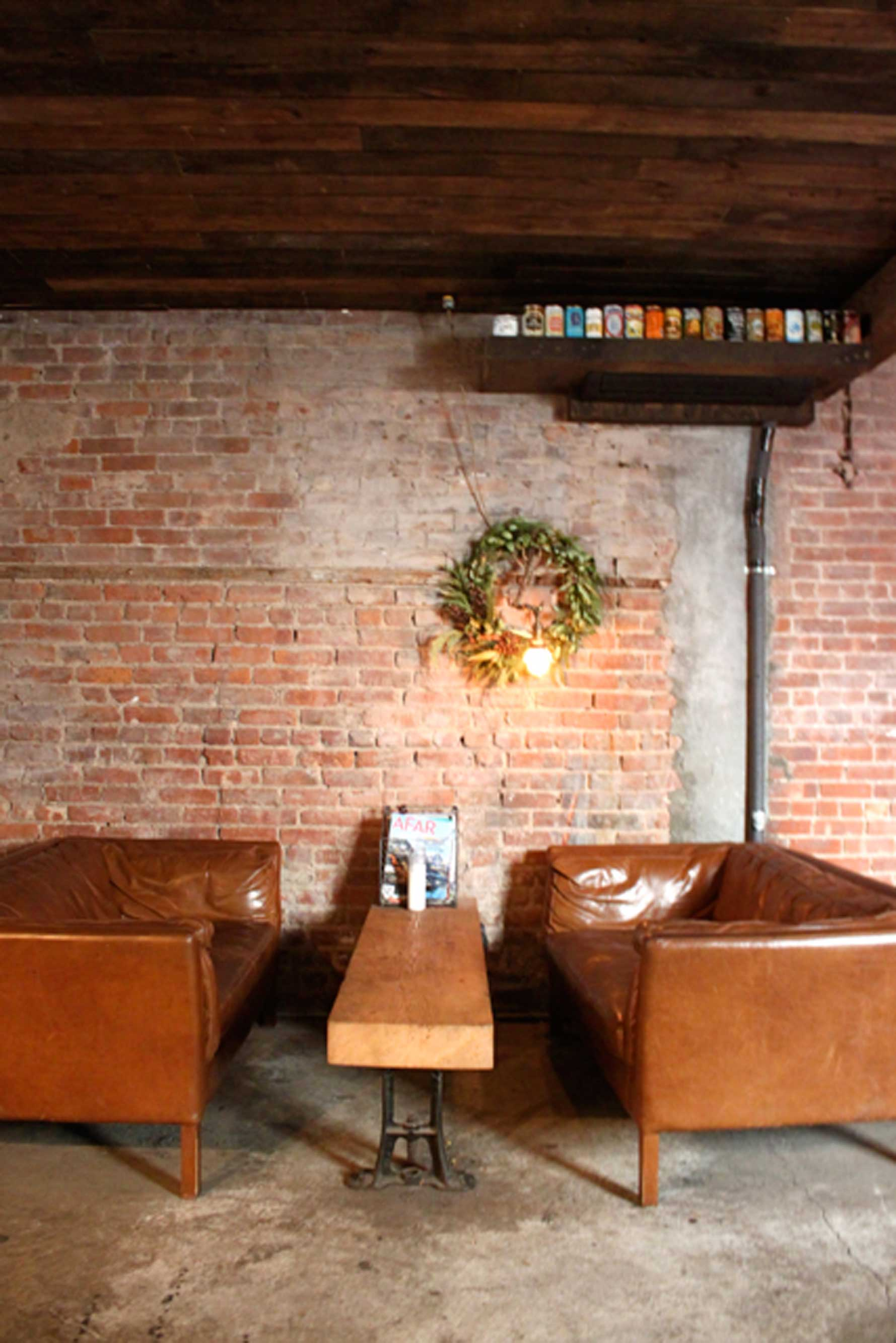 alphabet city beer co reclaimed wood table and leather sofas