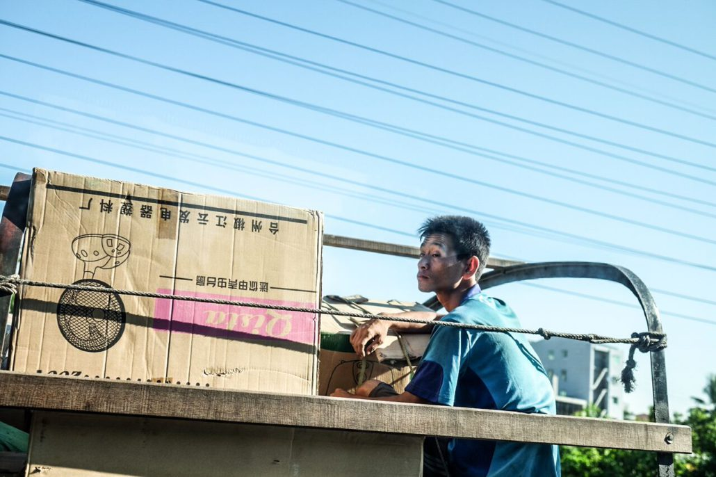 A young man in Myanmar riding on the back of a delivery truck.