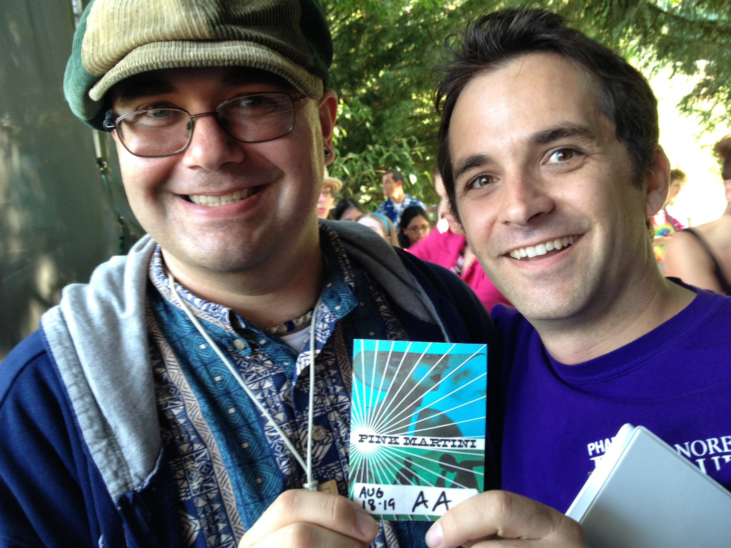 PHAME student Estin and Director of Arts and Education Matthew Gailey hold up a Pink Martini ticket