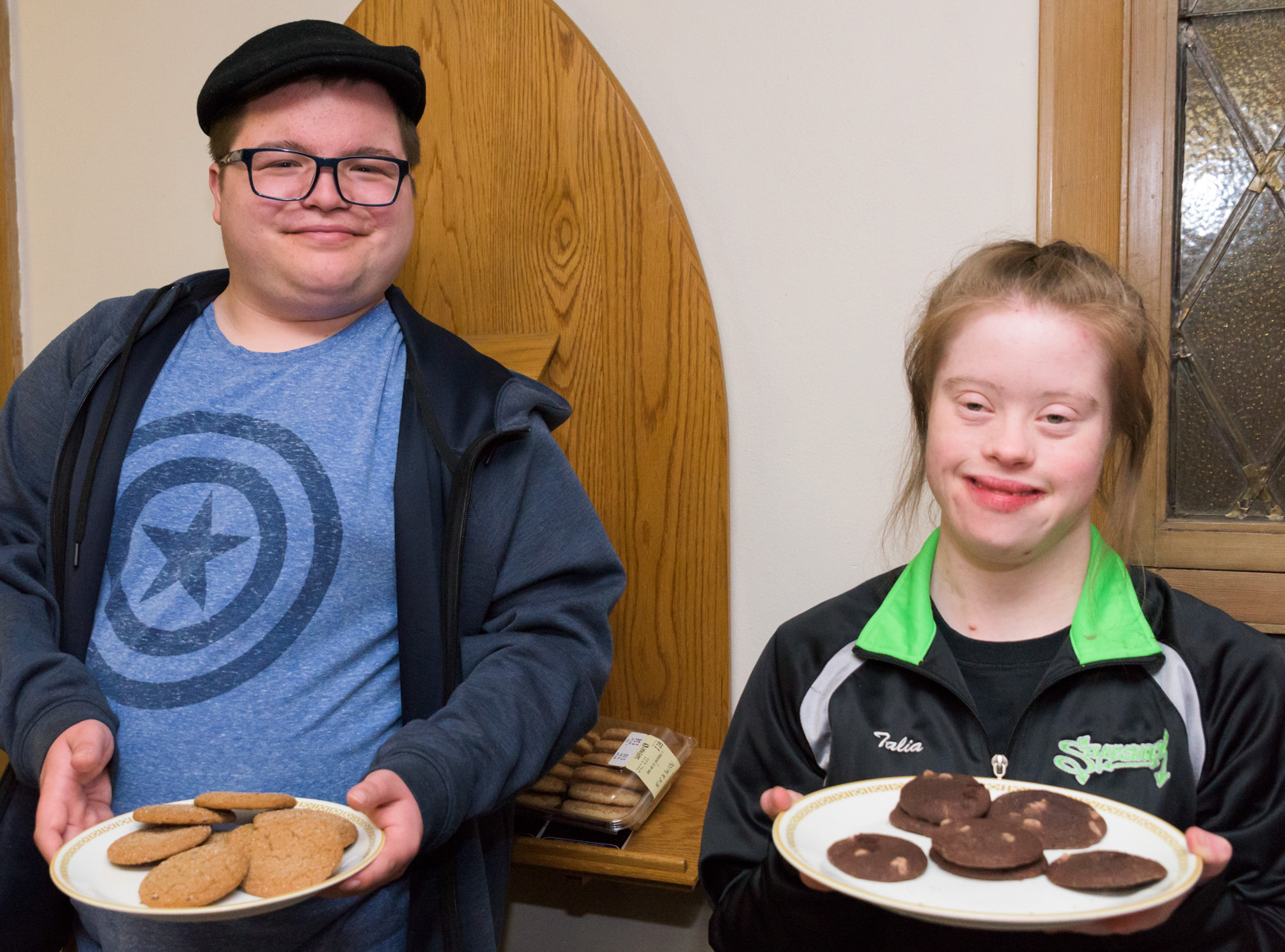 Two people hold plates of cookies and smile at the camera.