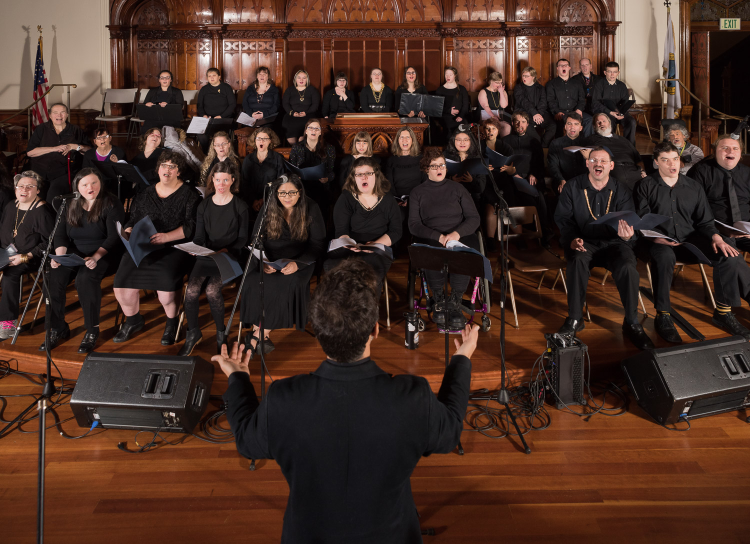 Man with his back turned to the camera directs a choir