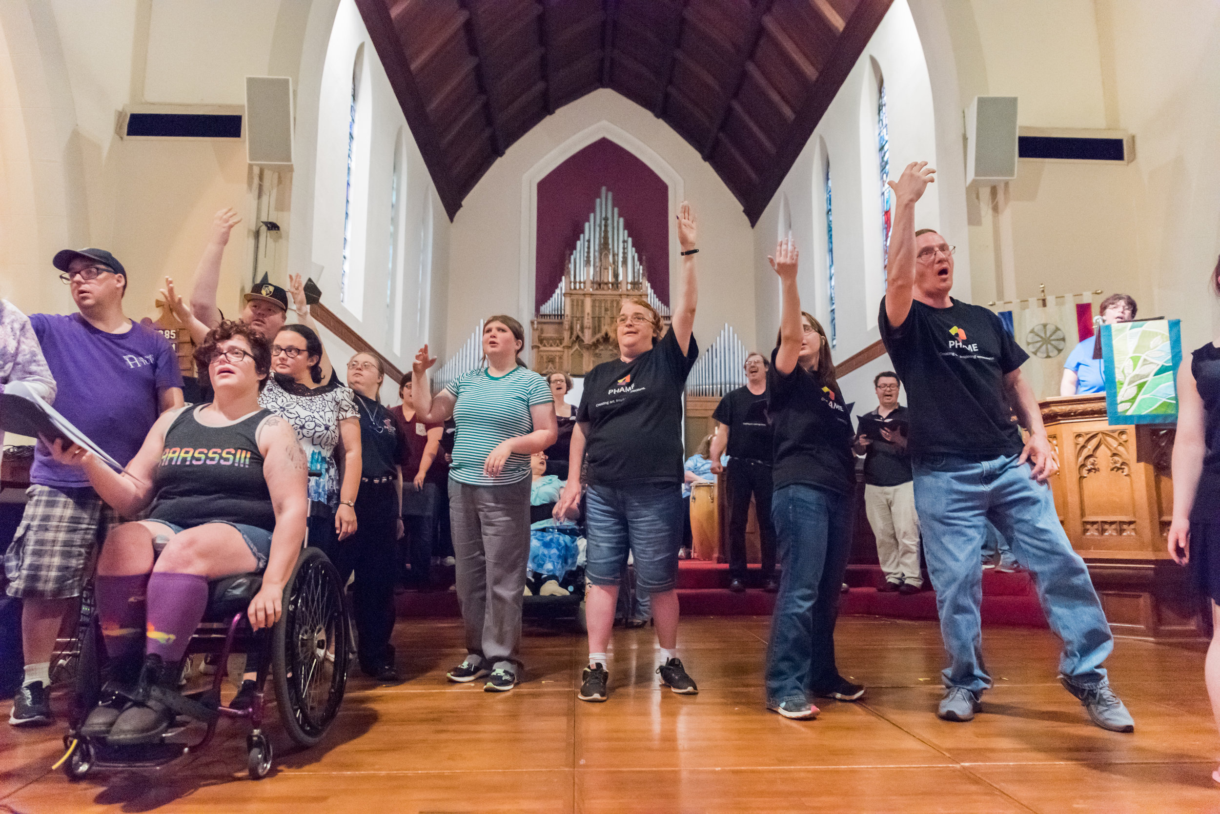 Group of people stand in large room with their arms raised, one person is in a wheelchair