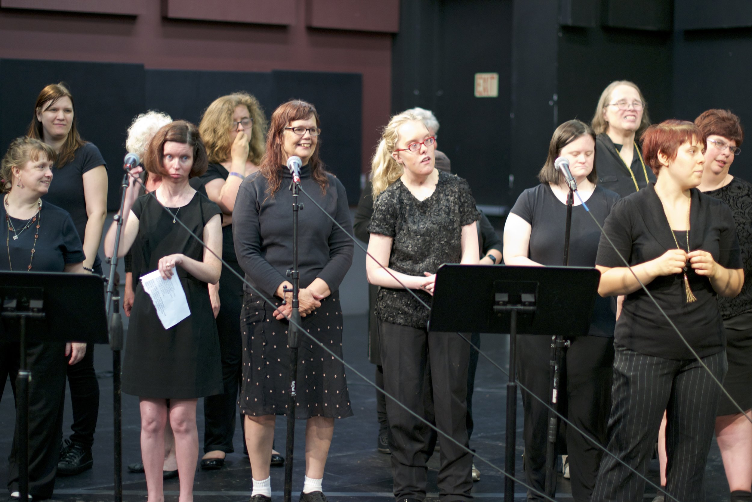 Group of women stand in front of microphones and a music stand