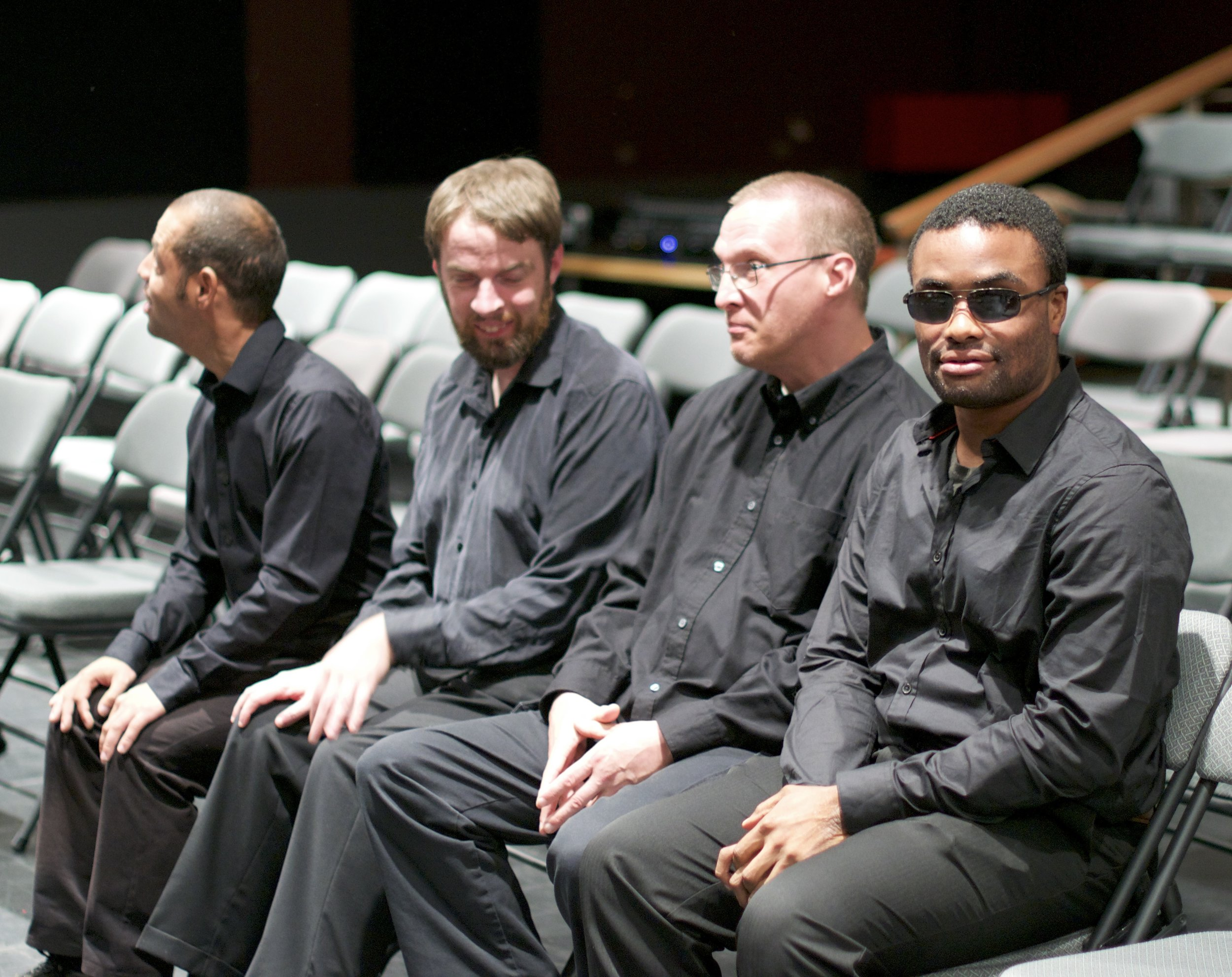 Four men sitting in folding chairs, wearing all black
