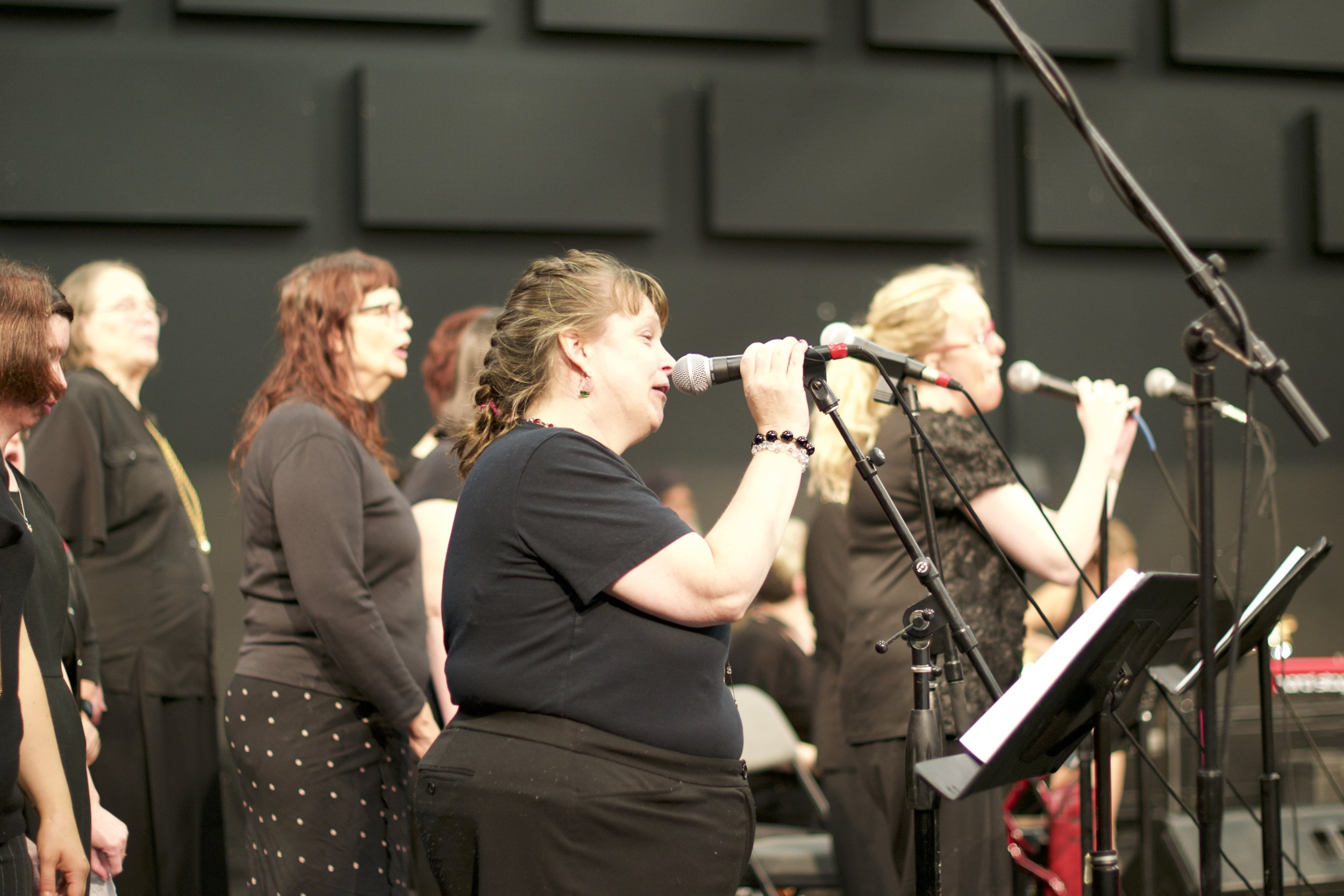 Group of women facing to the side and singing into microphones