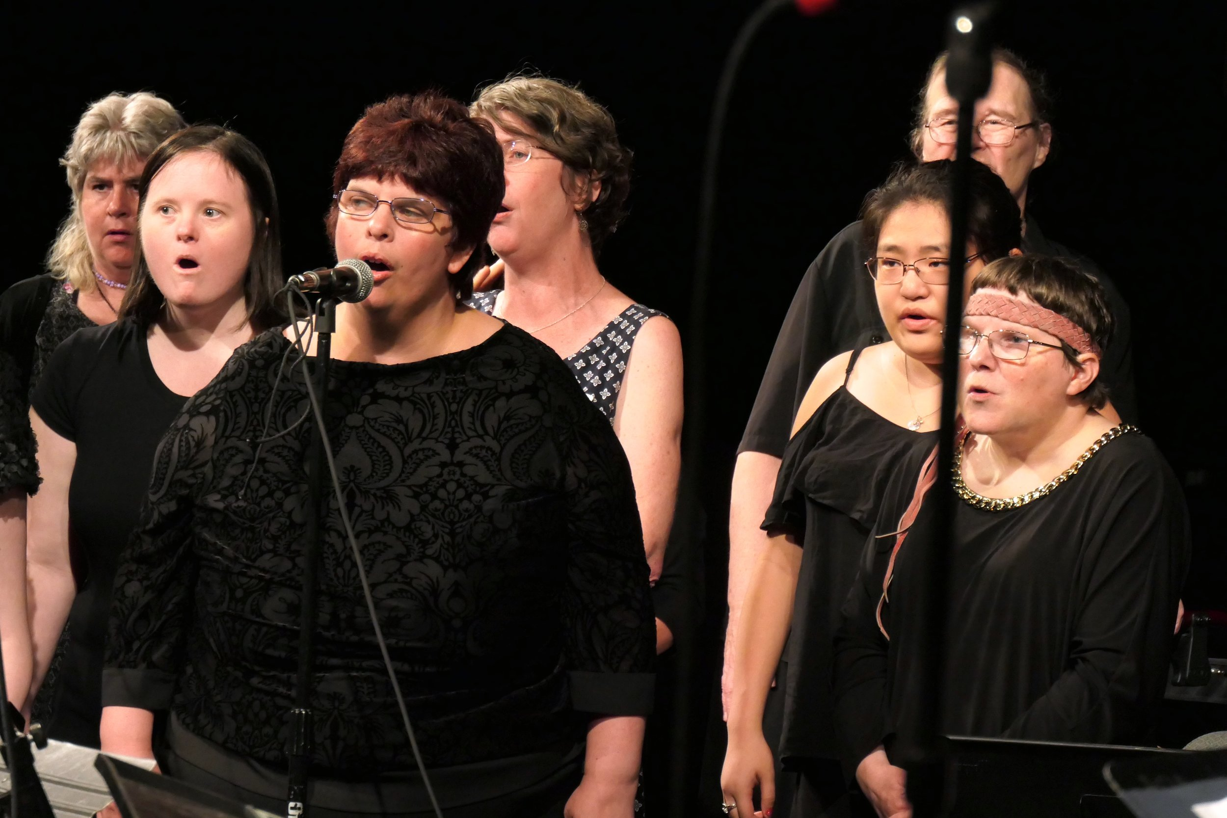 Group of women singing , some with microphones, in a dark room