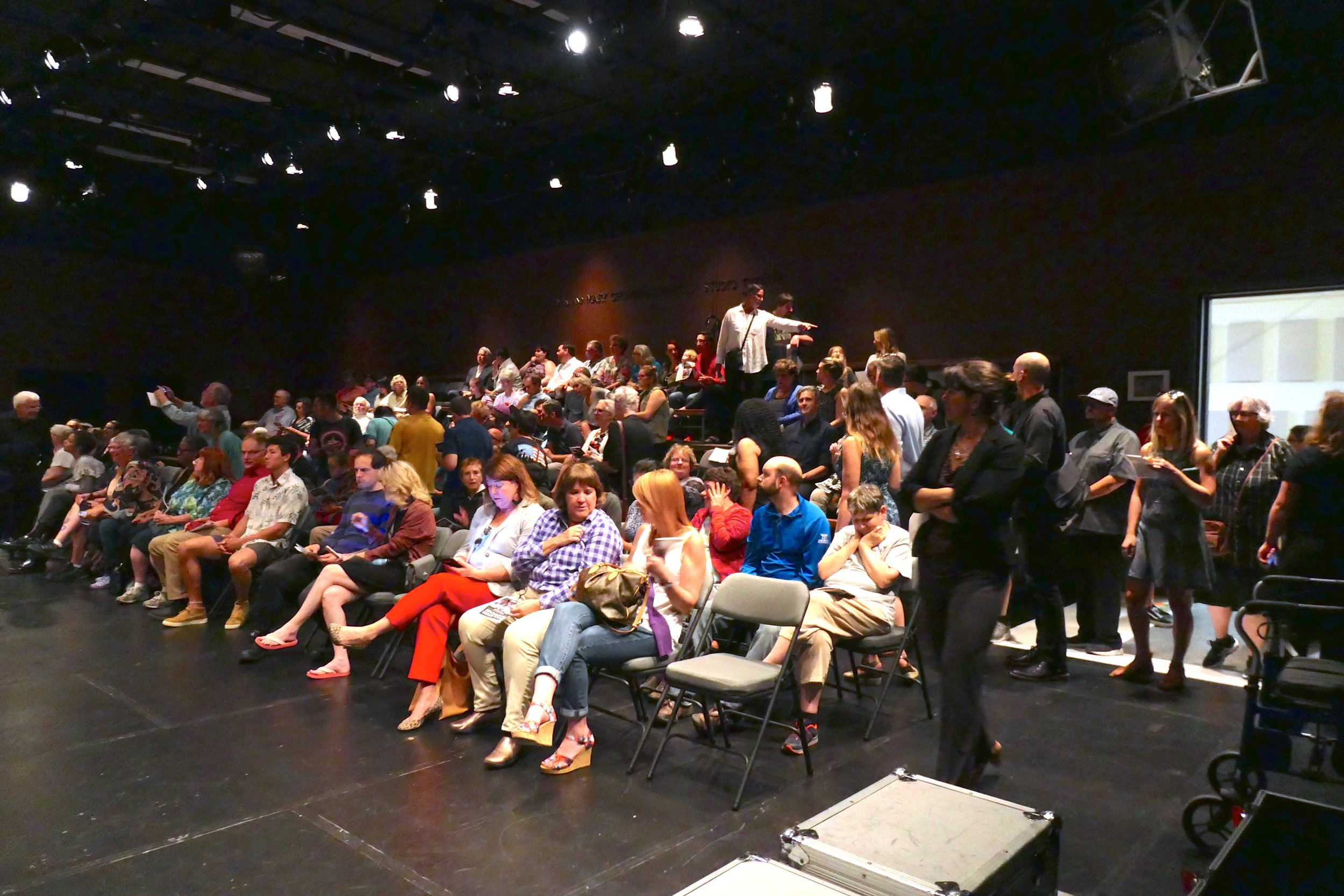Full audience of seated people in a black box theatre