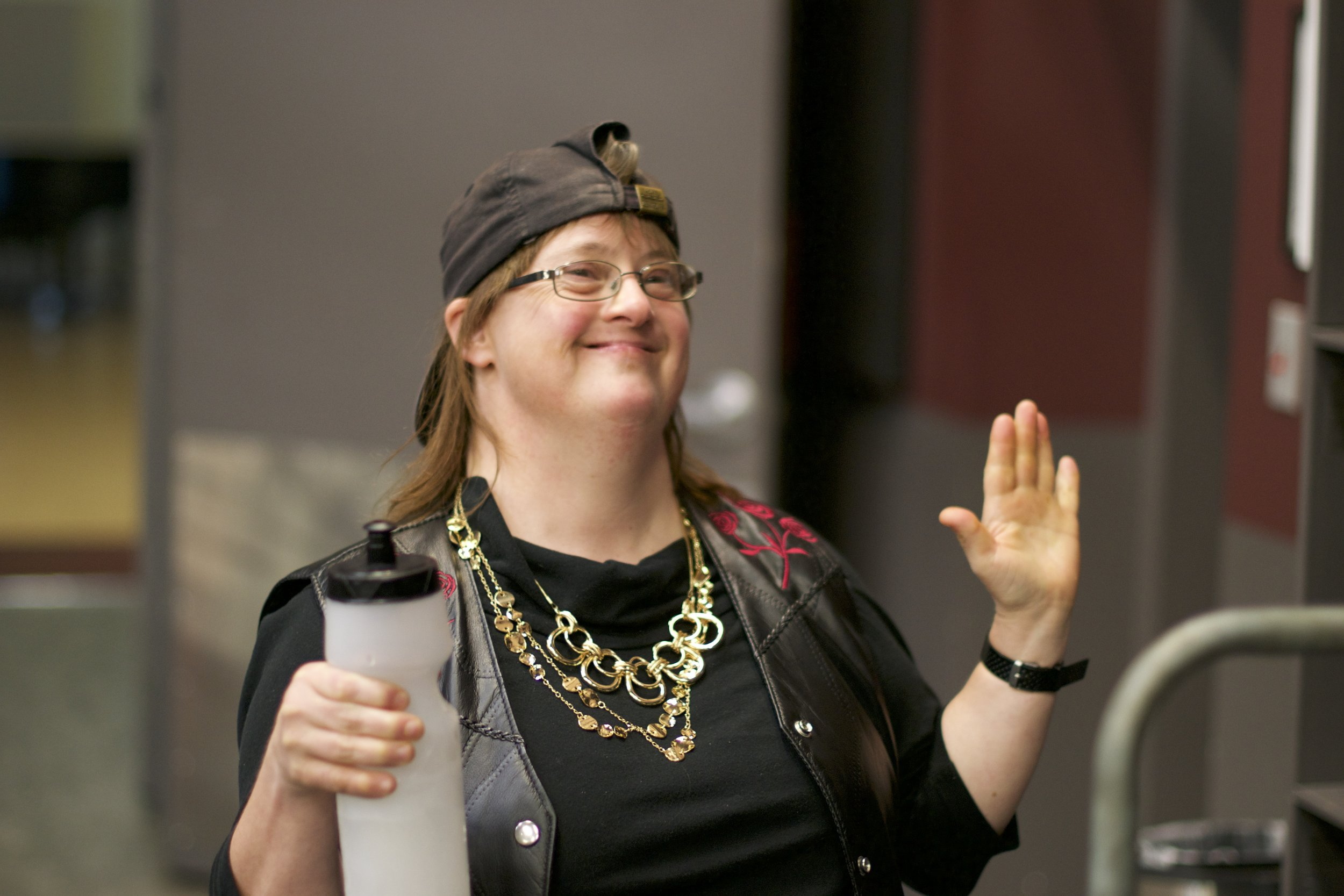 Smiling woman wearing backwards cap and gold necklace, holds a coffee cup and raises the other hand