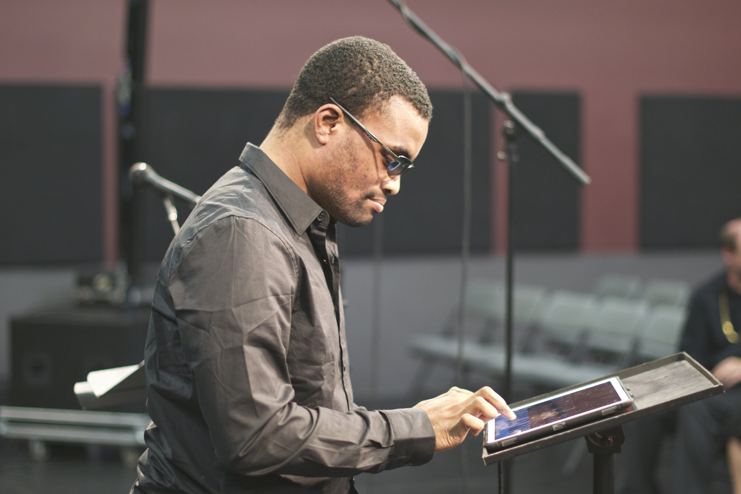 Man with dark glasses seen from the side, touching an ipad which sits on a music stand