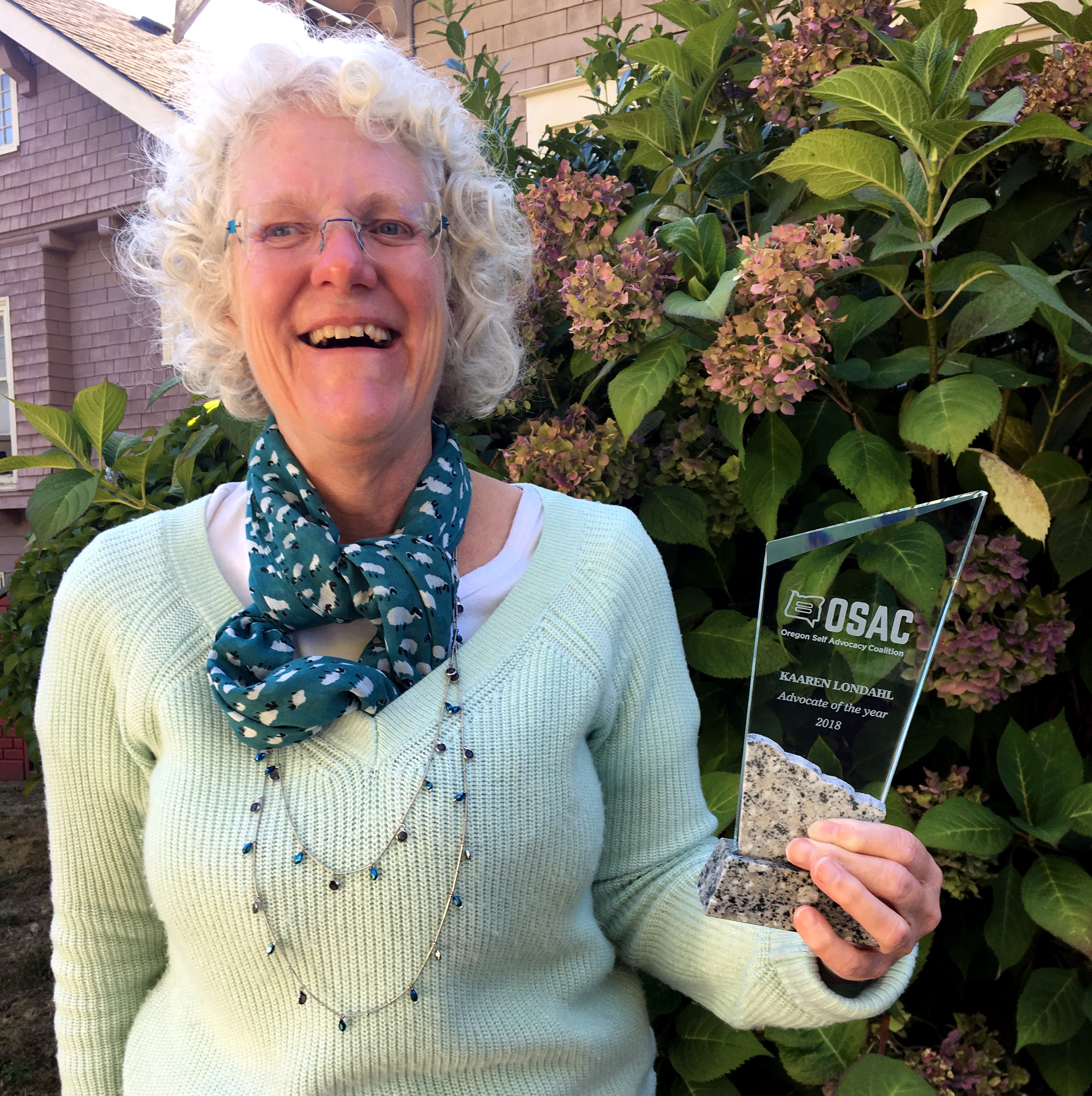 White haired woman with glasses standing in front of a bush holding a clear glass award