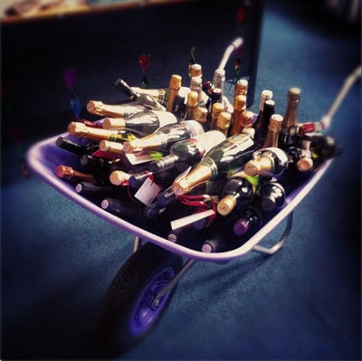 A wheelbarrow full of wine bottles.