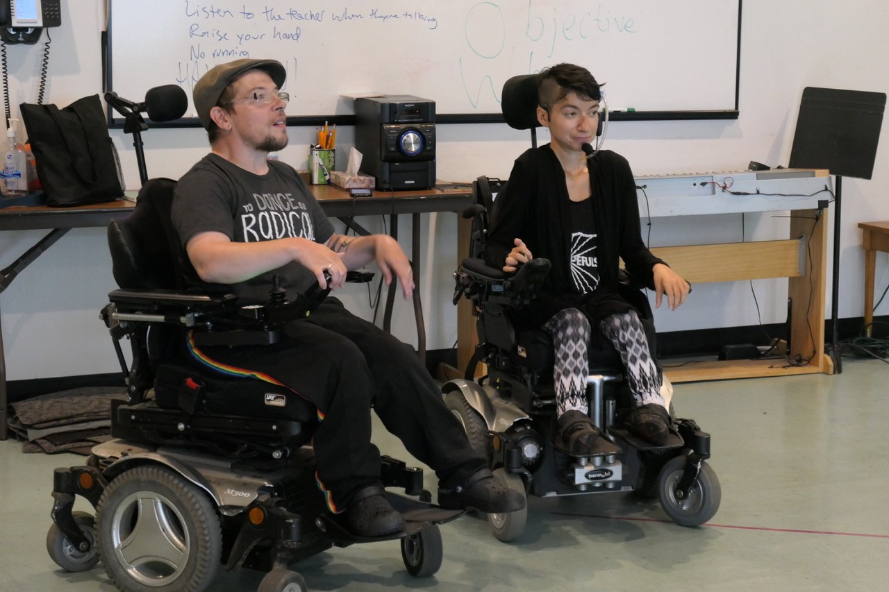 Two people wearing dark fashionable clothes seated in wheelchairs.