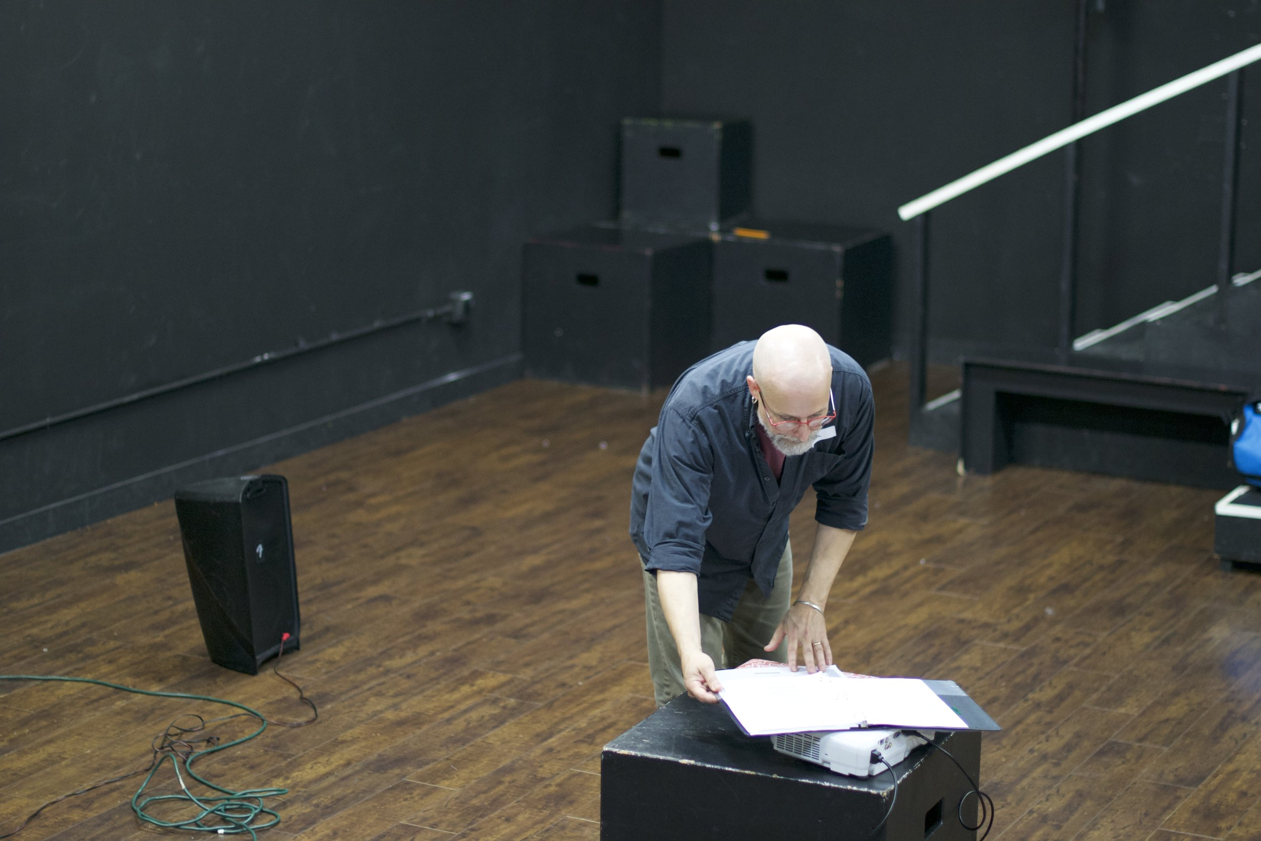 Man bending over in a black box theatre