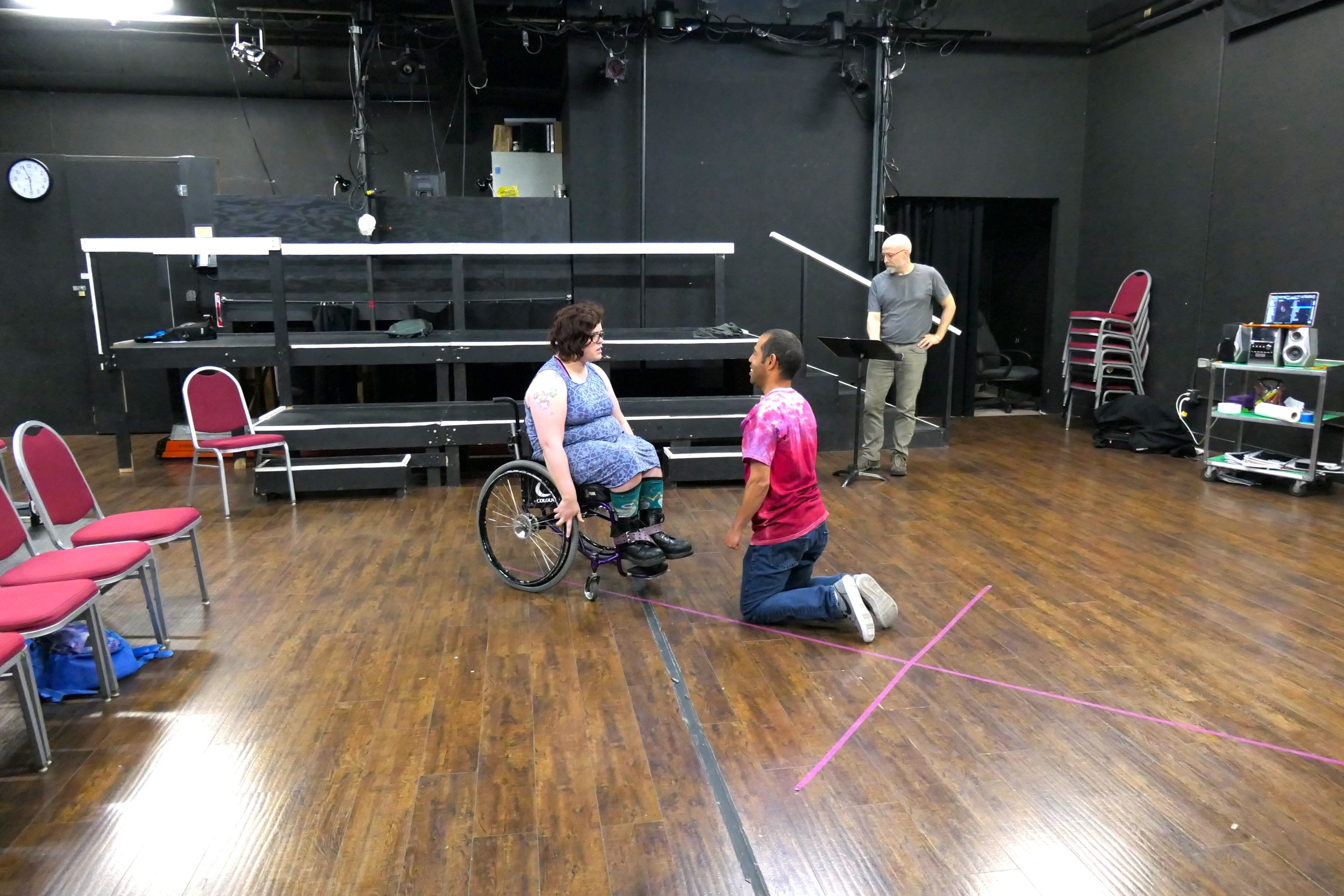 Three people in a black box theatre acting out a scene
