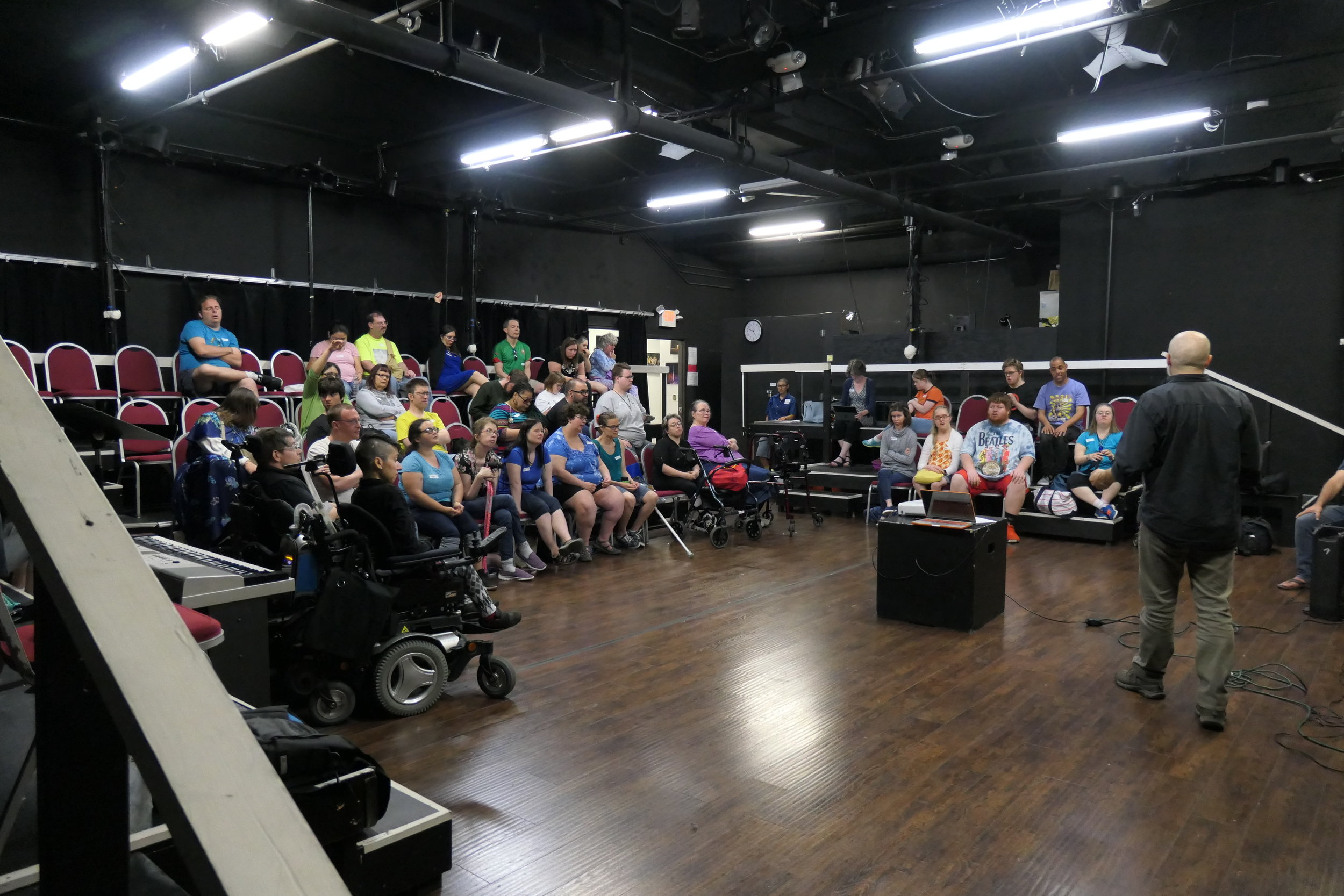 Man speaking to a large group of seated people in a black box theatre