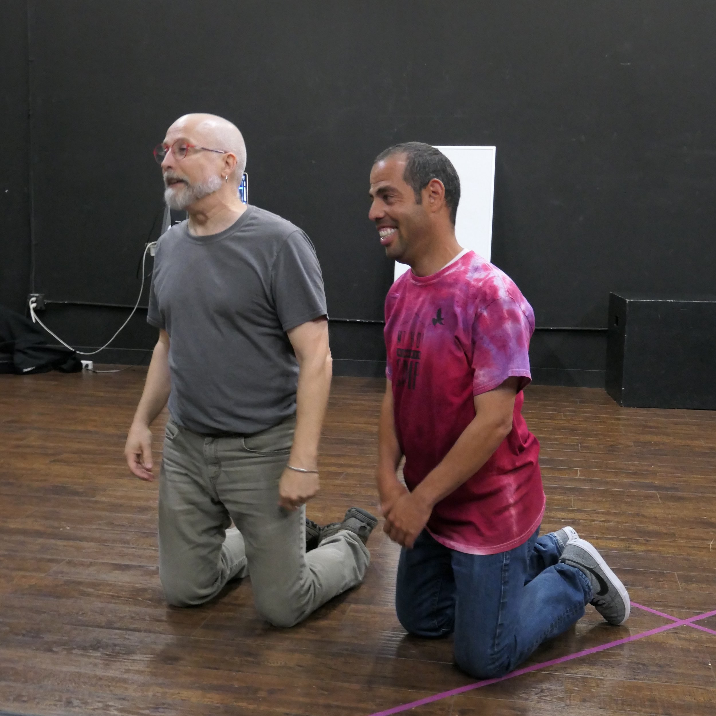 Two people kneeling in a black box theatre