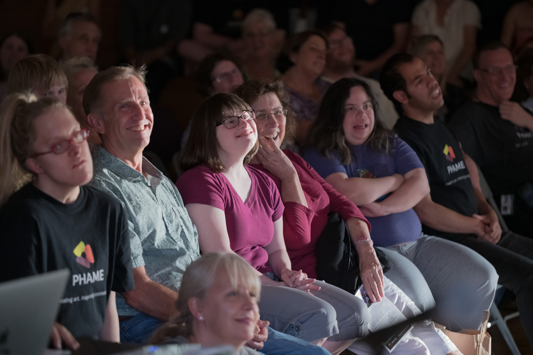 Group of people seated and happily watching something to the right