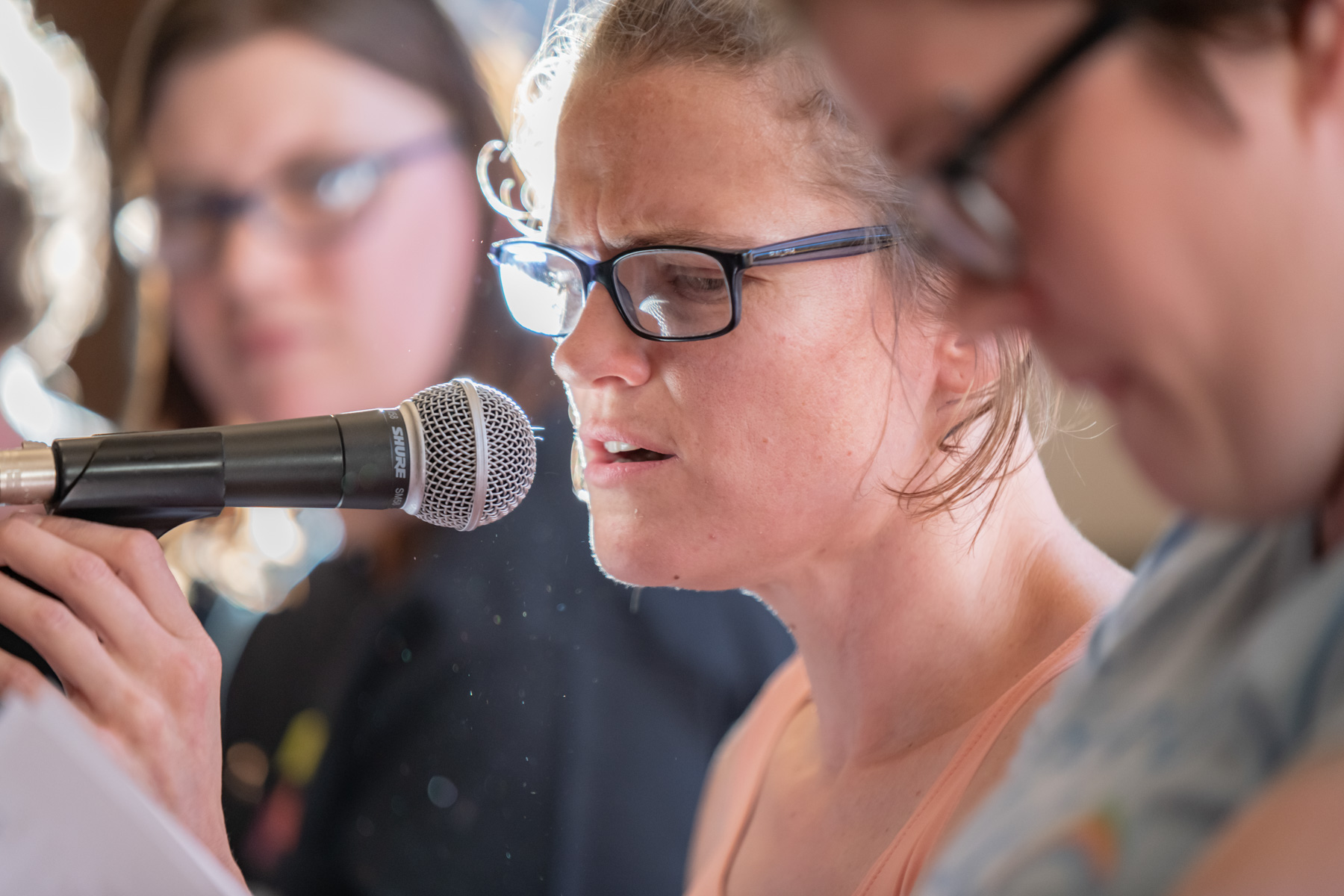Woman in glasses speaks into microphone.