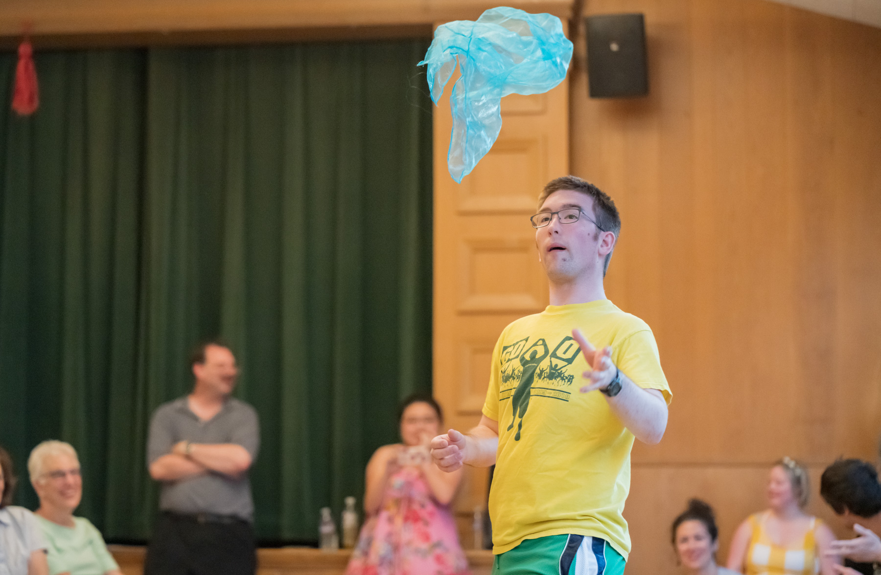 Man in yellow t-shirt throws a circus scarf in the air.