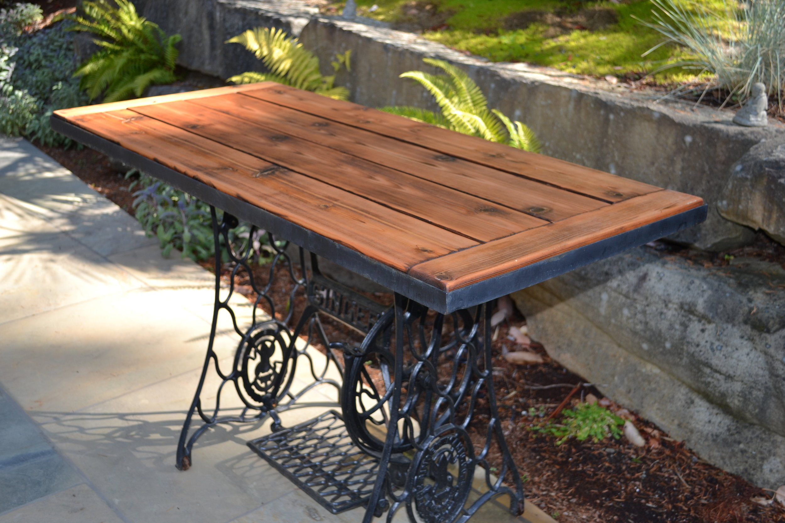 Cedar outdoor table on antique cast iron sewing machine base. Ancient Japanese Shou Sugi Ban torched finish. Sold.