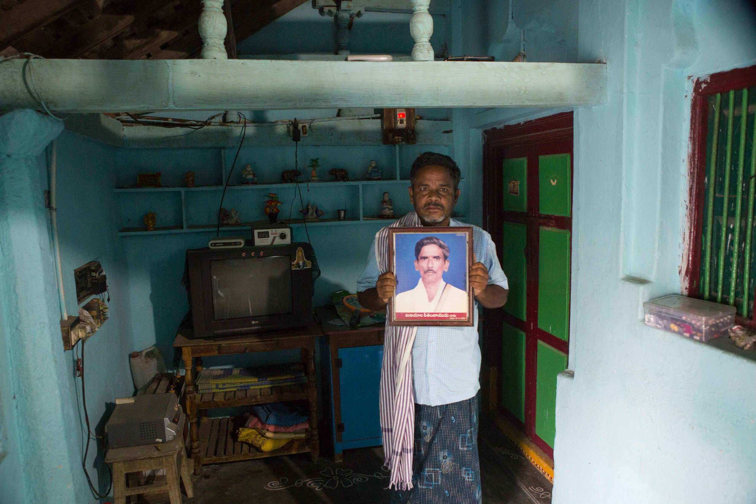 A man stands with his fathers portrait who passed away. He is the single earning member of his family. He is fighting with vision loss. A village in Vizianagaram, Andhra Pradesh