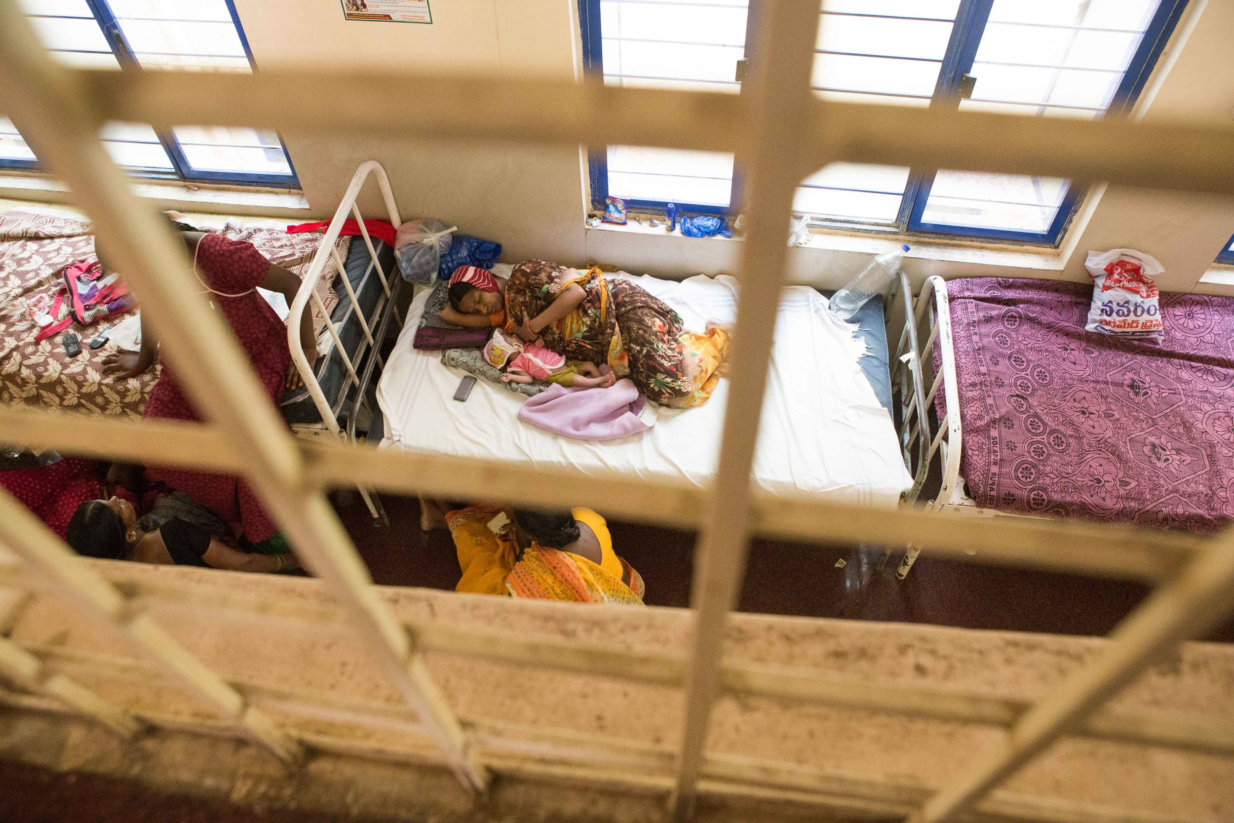 Sometimes there are not enough beds in the district hospital to accommodate the huge demand. The hospital graciously provides a temporary bed to a mother and a new born child in it's corridor. Nalgonda District Hospital, Telangana