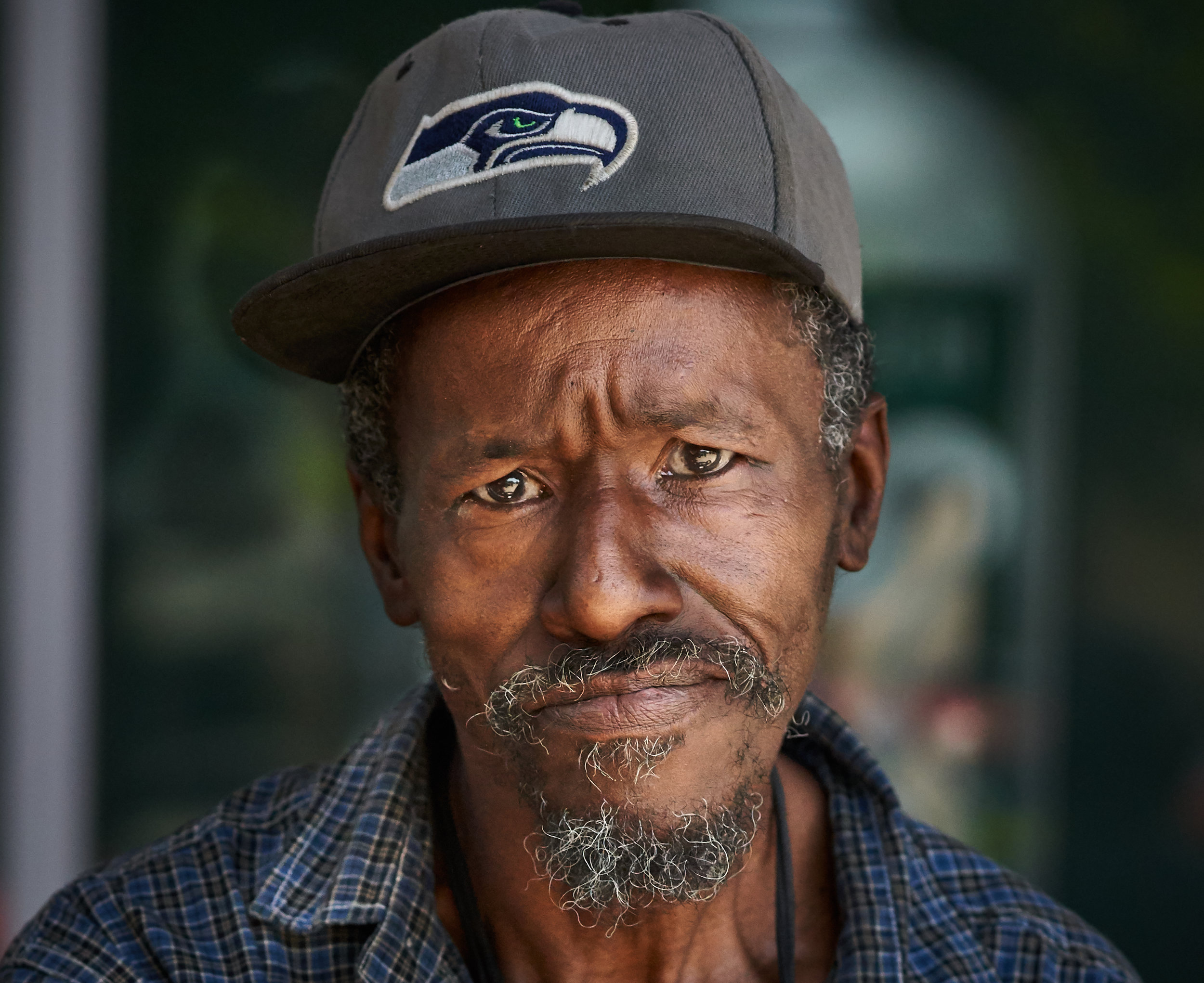 "Meet Larry, he is a local Real Change vendor who has been here since 1981, he moved from Texas here to Seattle. I sat down with Larry and had a discussion with him about his life and the heat that Seattle is experiencing at the moment. I personally prefer the heat, and we had a laugh about him being from Texas and how people like to complain about the heat in the Summer here. As you know it gets very hot in Texas. I asked him if he ever missed Texas and he said ""Everybody misses home from time to time."" Thanks for your time Larry and for doing what you do."