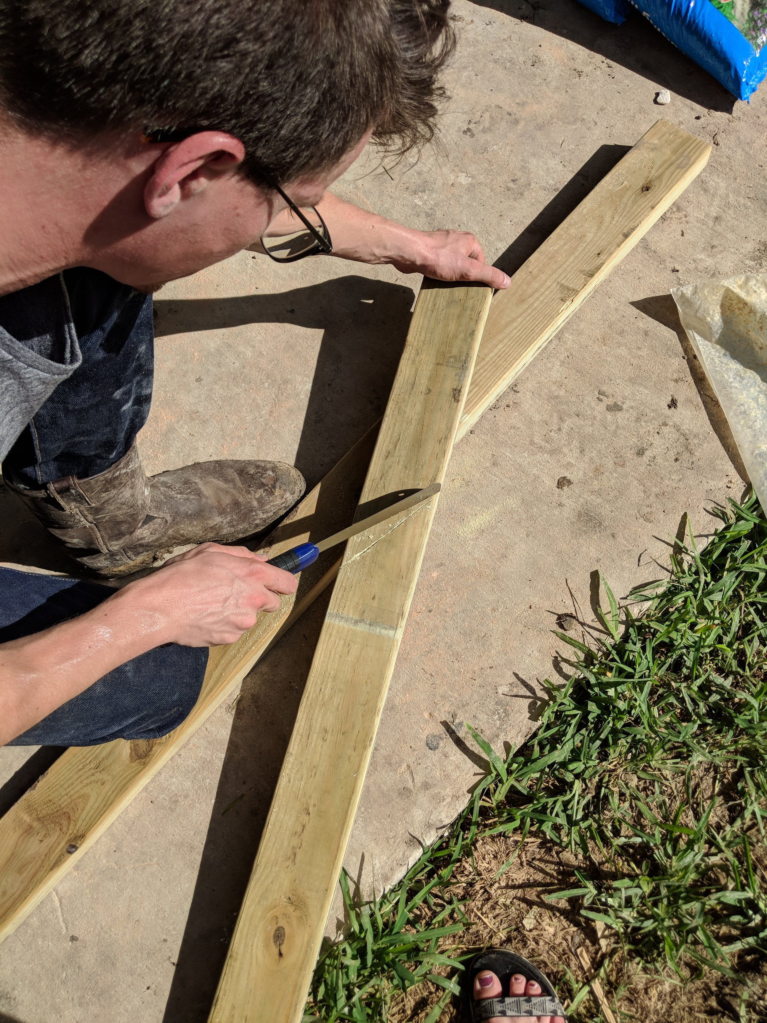 Michael made stakes by sawing a sharp angled piece off of the 2x4.