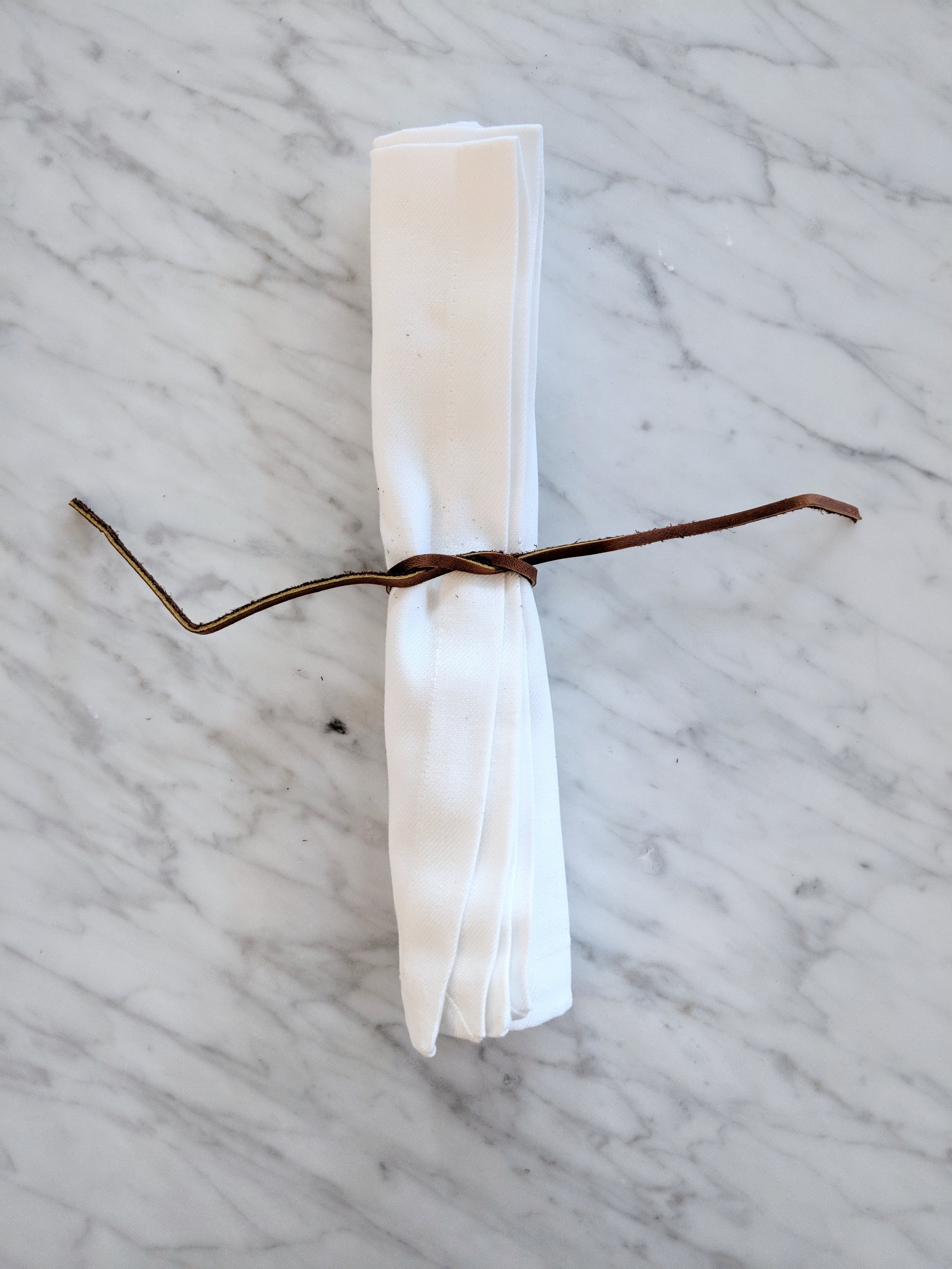 Tie a super simple knot at what will be the back side of the napkin.