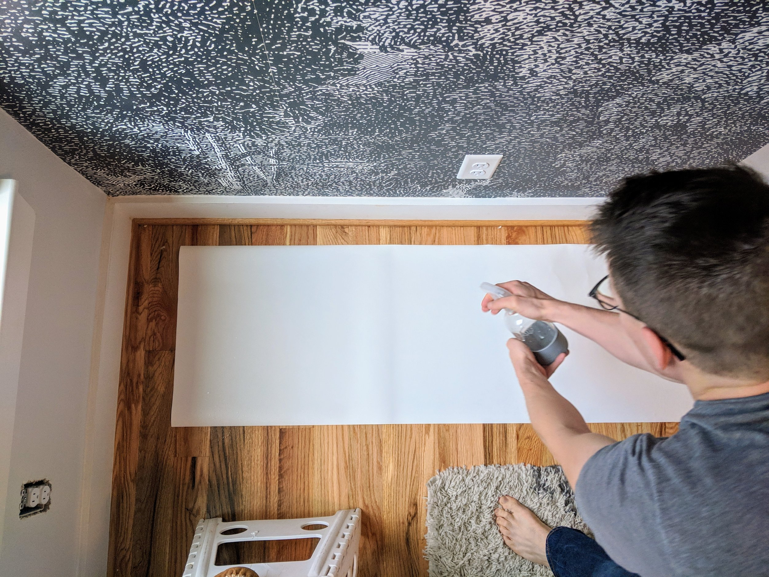 Installation requires laying the paper on a flat surface and misting the wallpaper with a spray bottle.