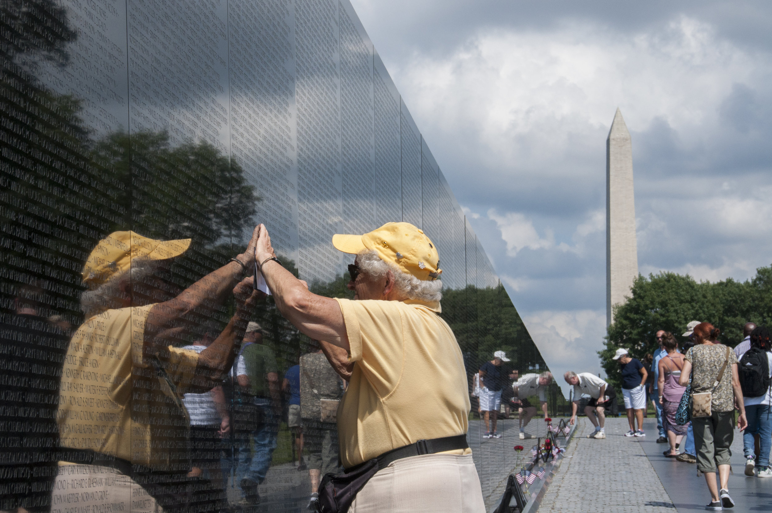 "Since the wall was built, ""rubbing"" has become a tradition to honor veterans. Anyone who is interested in receiving a rubbing of a particular name can ask volunteers in yellow to send the small piece of paper to any address."