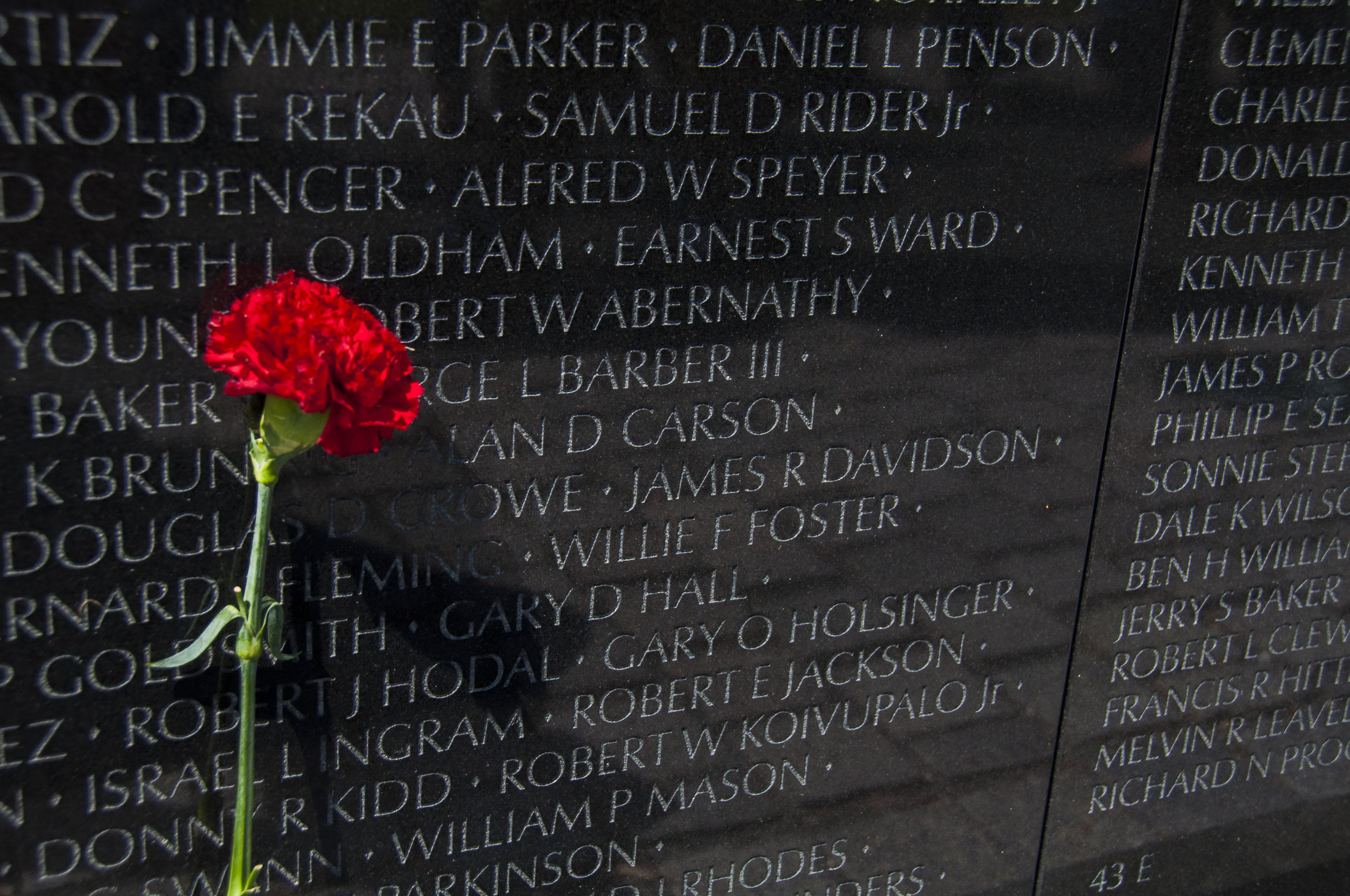 Even decades after the war, visitors to the monument are still compelled to bring fresh flowers to honor the engraved names.