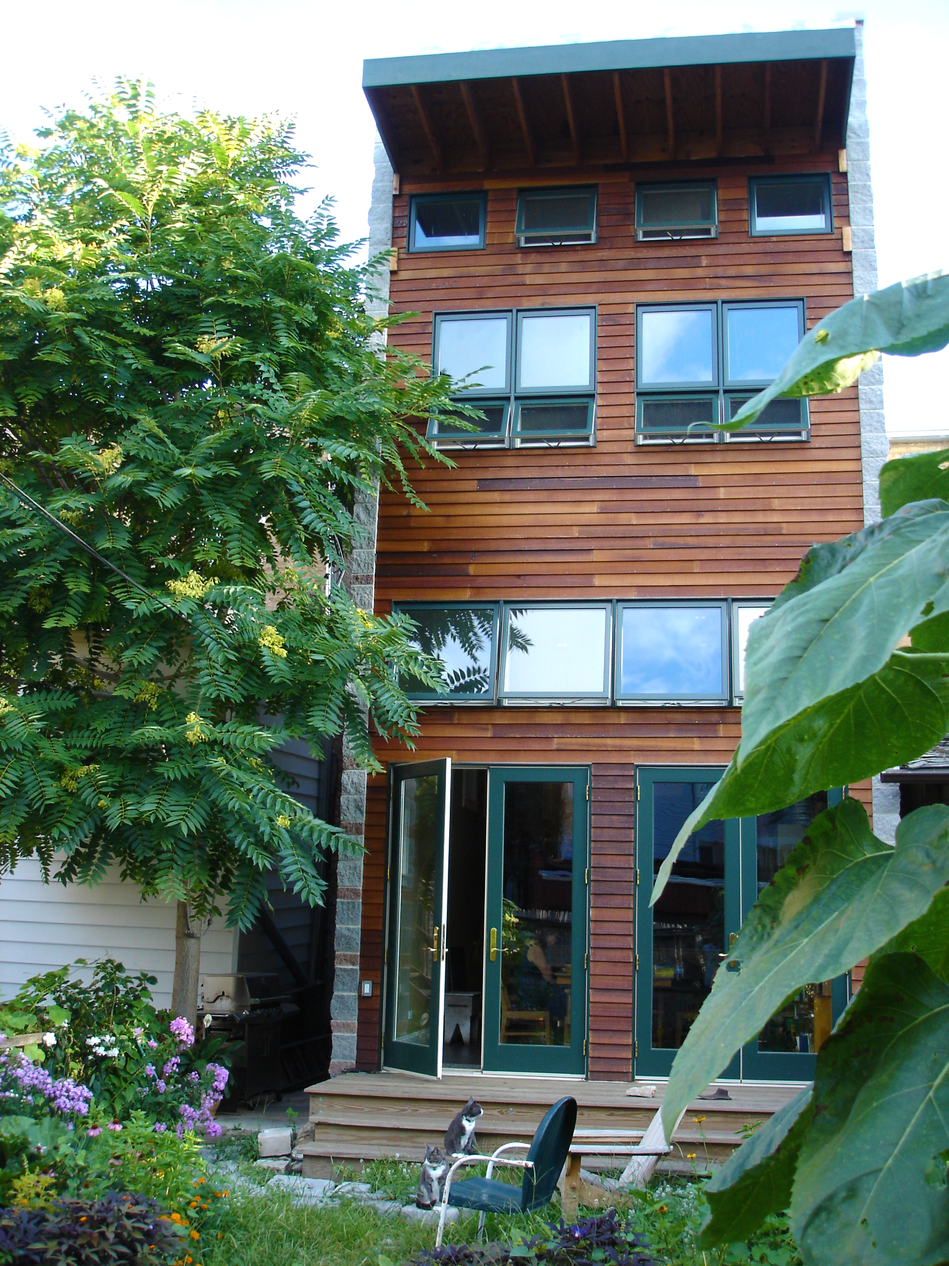 modern addition on 1890s single-family brick rowhouse, french doors open to garden