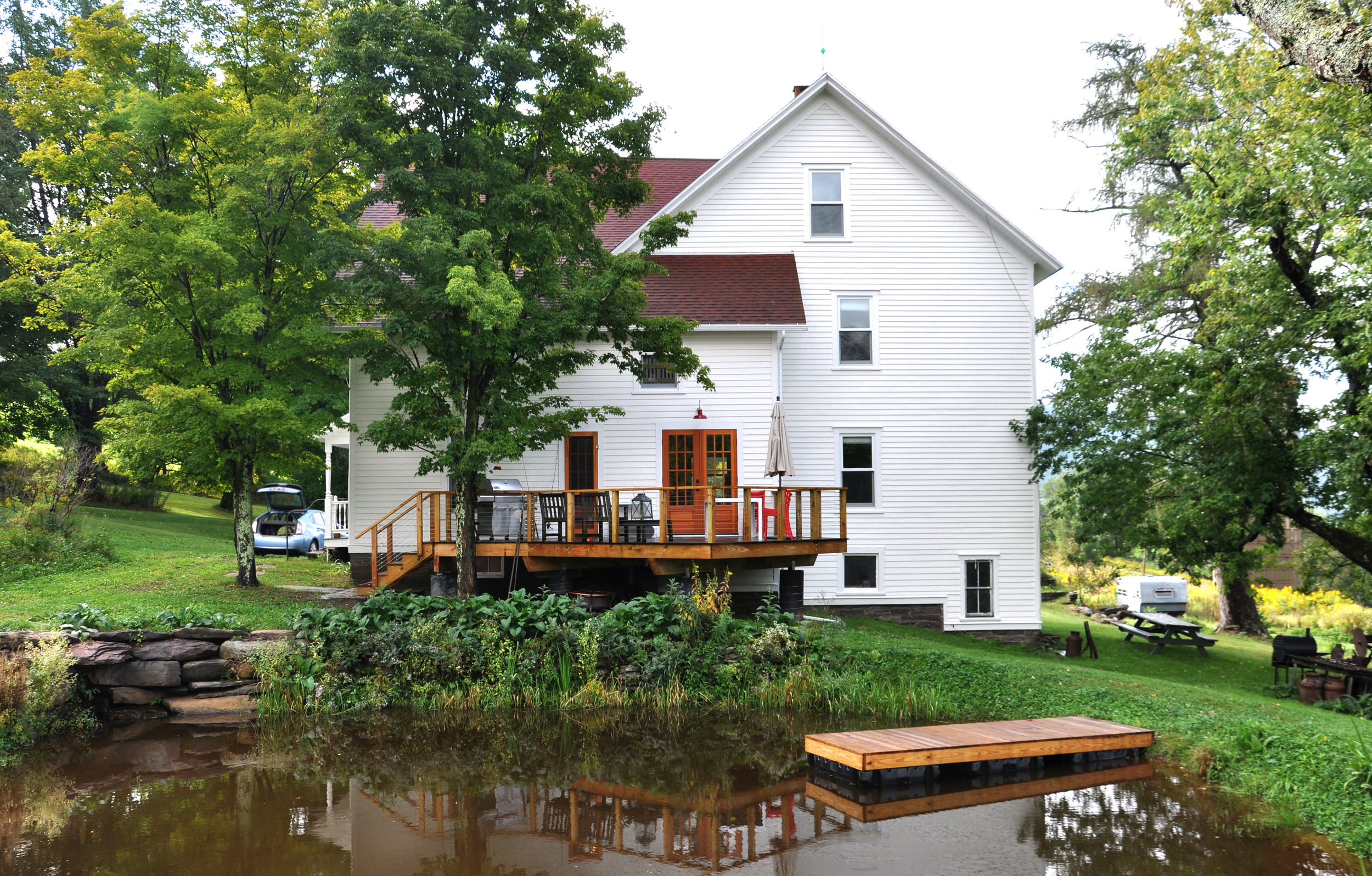 modernized rural farmhouse, residential renovation, deck, porch, outdoor dining, mountain home, pond