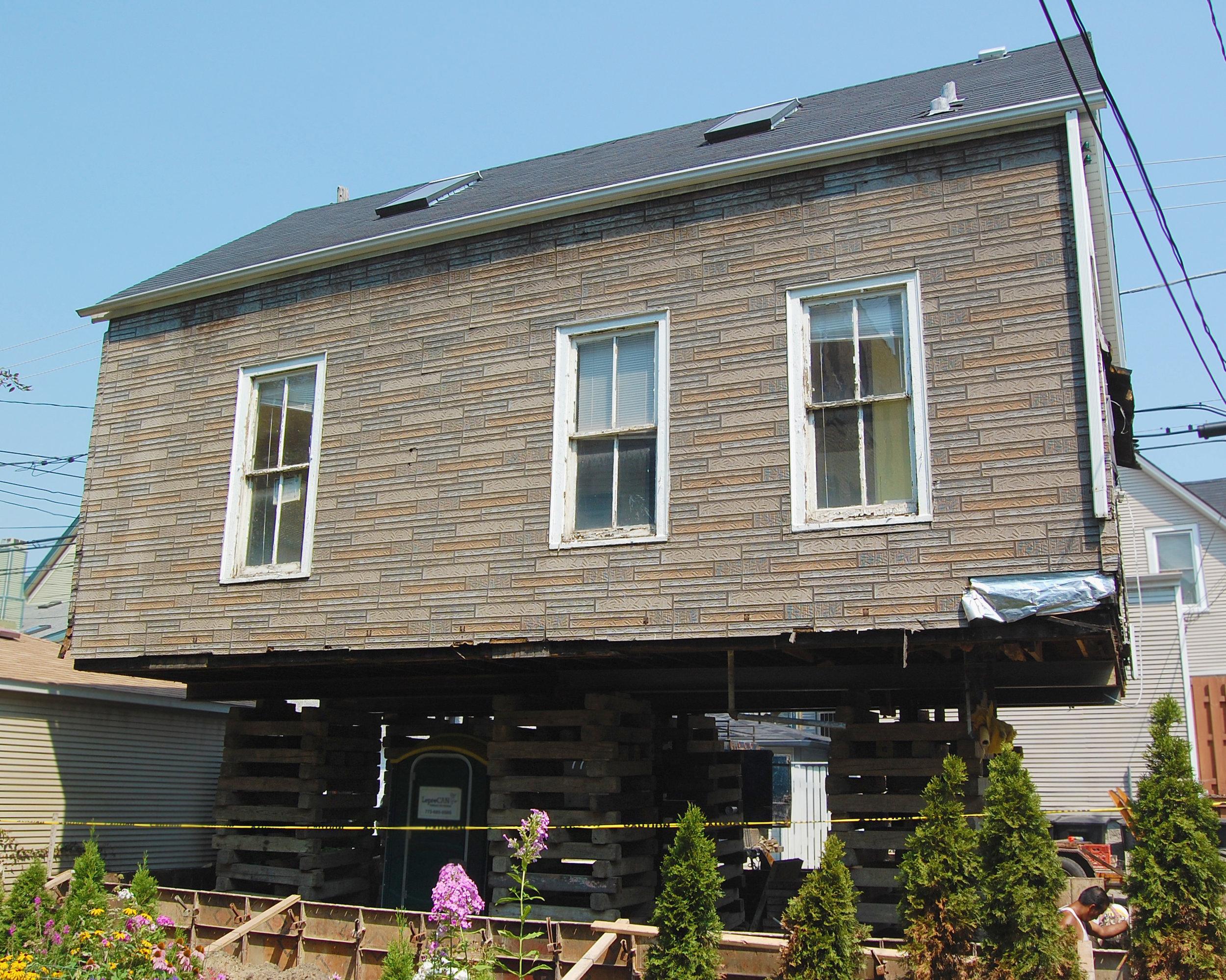 custom gut renovation single-family late-ninteenth-century coach house residential home, building raised on stilts, under construction