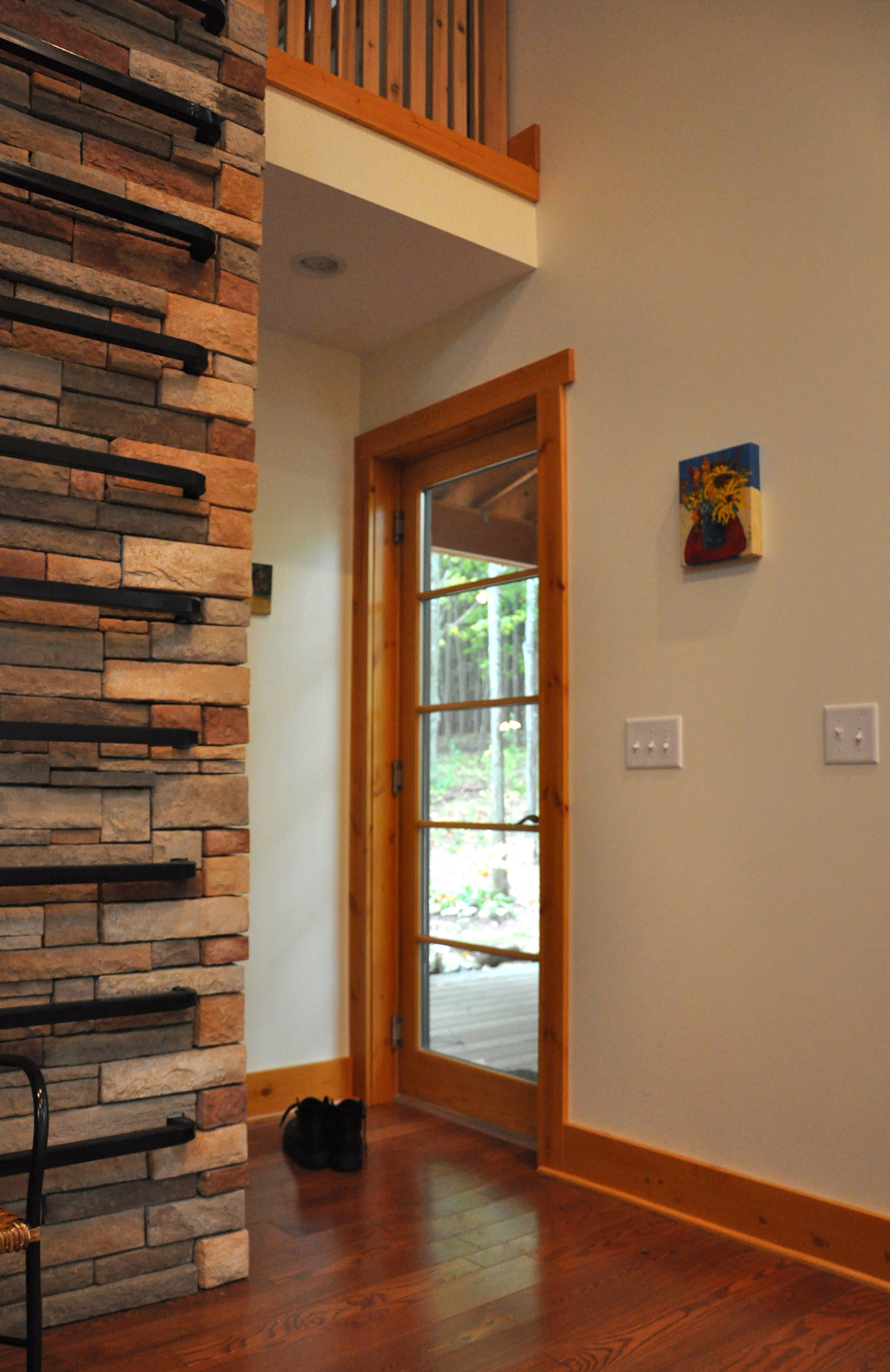 back door to porch, ladder on stone wall to loft, wood floors