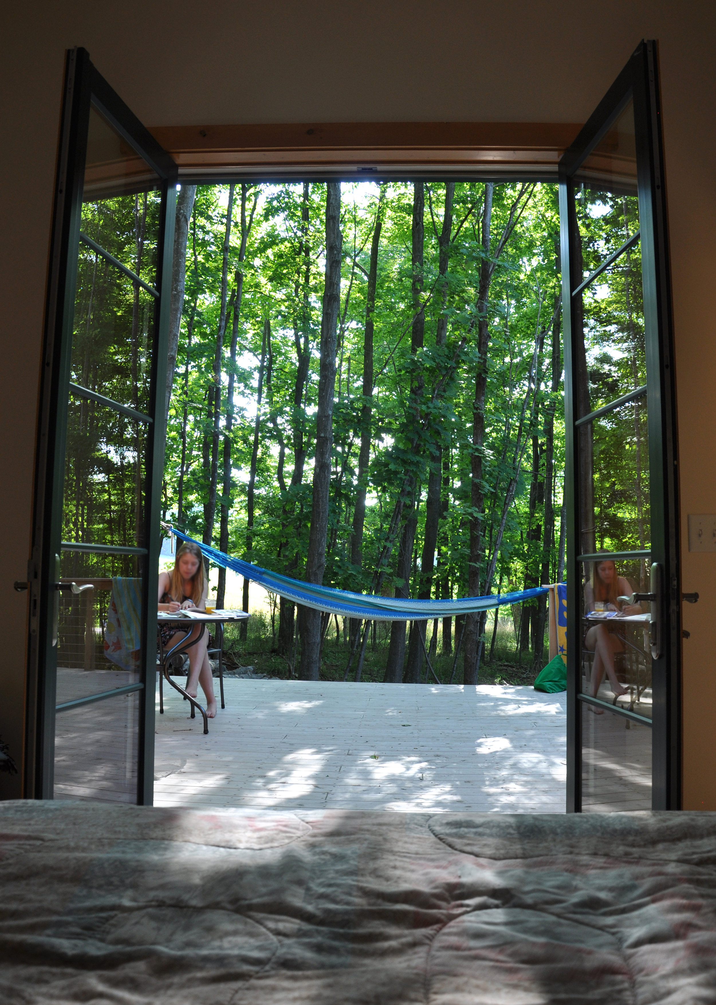 view from master bed out french doors to patio with hammock and table, green trees, forest