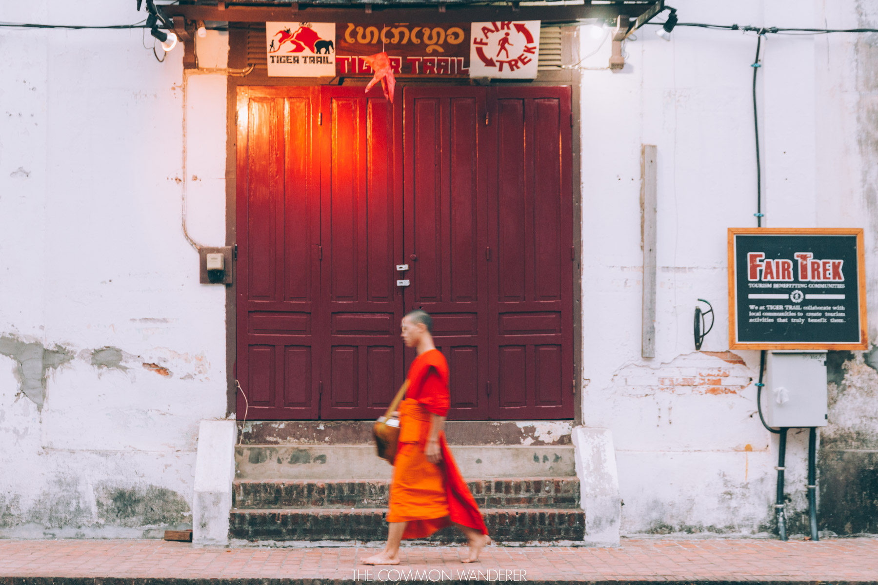 a young monk walks past a door on the way to morning alms, Luang Prabang