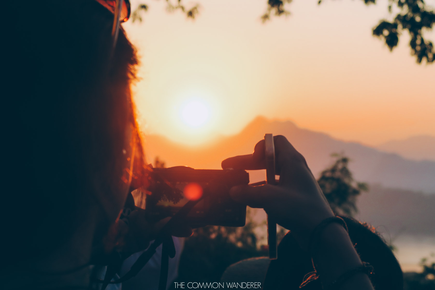 A women taking a photo of the sunset on Phousi Hill Luang Prabang
