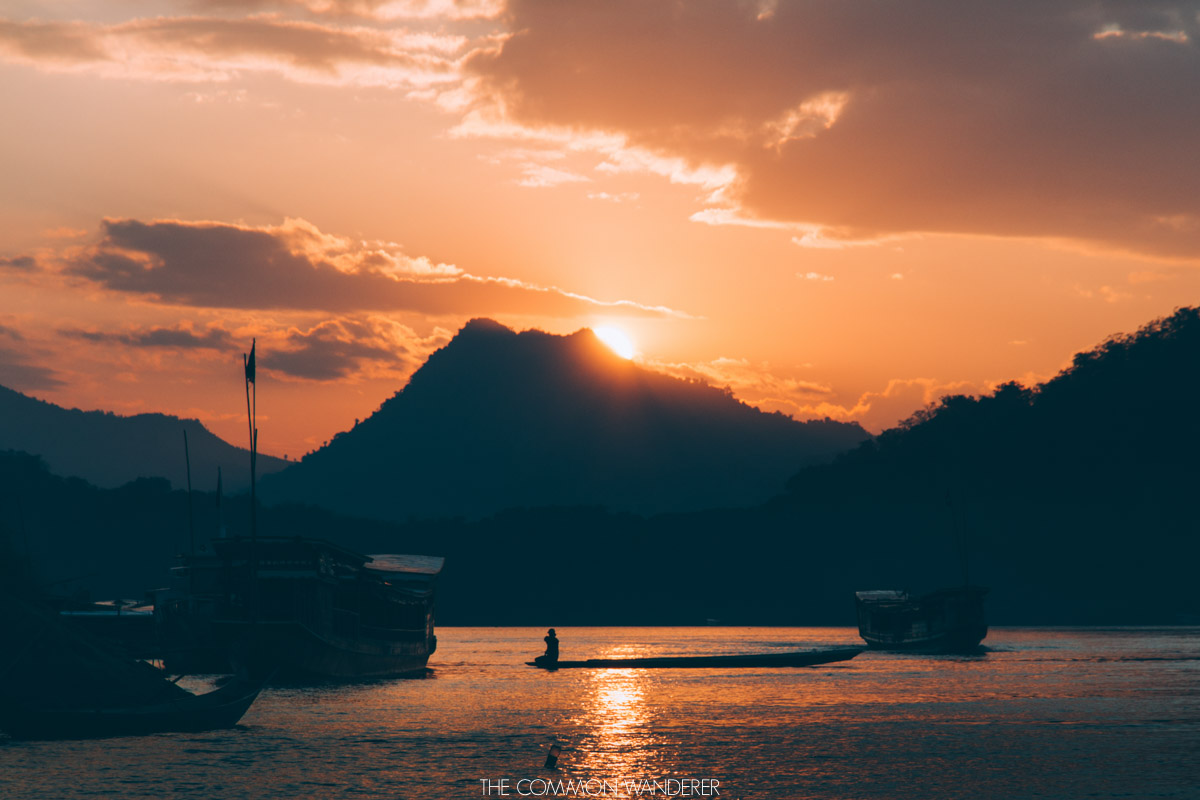 a fisherman sits on his boat as the sun sets over the Mekong River, Luang Prabang - best destinations to visit in 2018