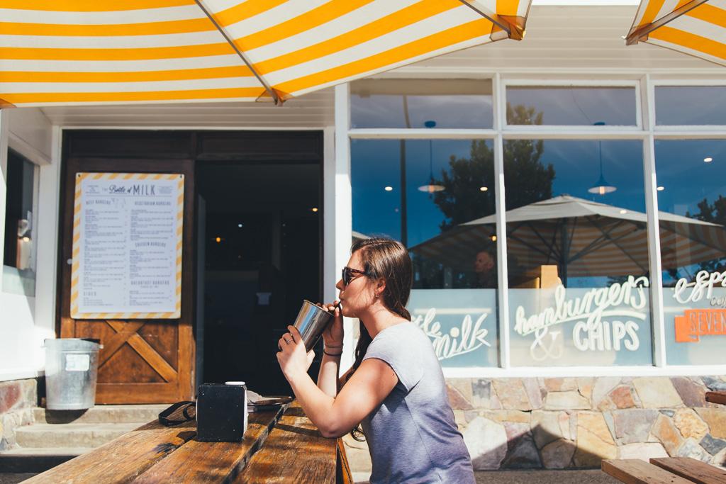 A woman drinks a milkshake at Bottle of Milk, Lorne, Victoria