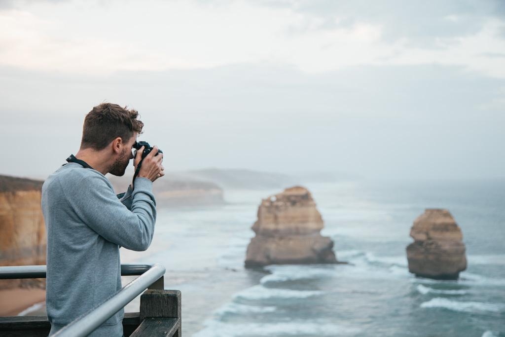 A man photographs the 12 Apostles, Port Campbell National Park, Victoria, Australia