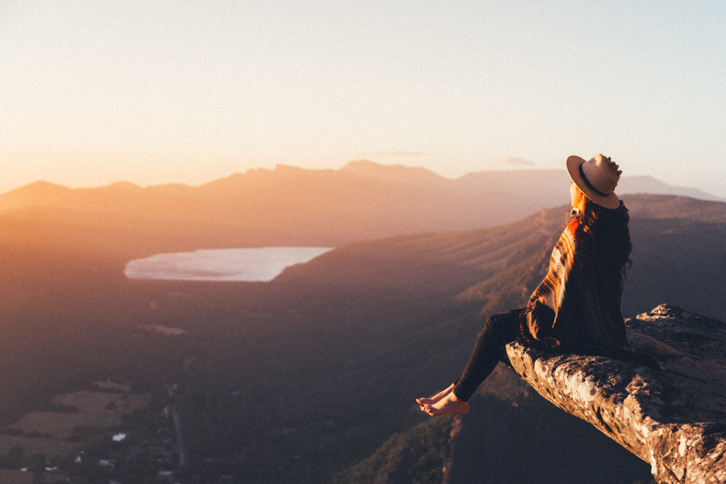 A woman watches the sun rise from Boroka Lookout, The Grampians