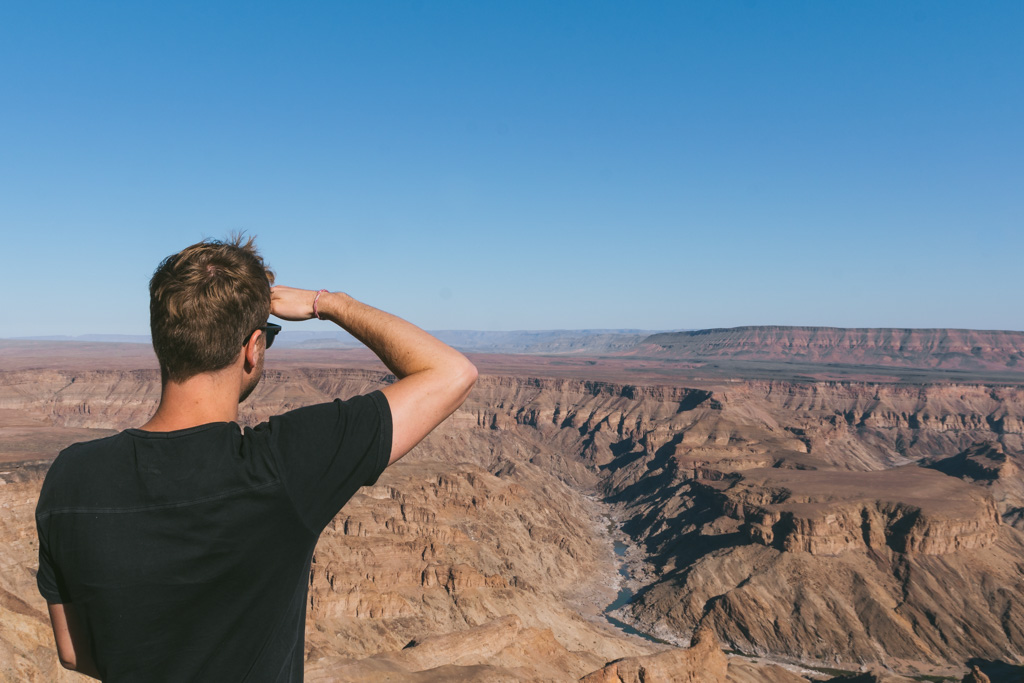 Man overlooking Fish River Canyon - Namibia Travel Guide