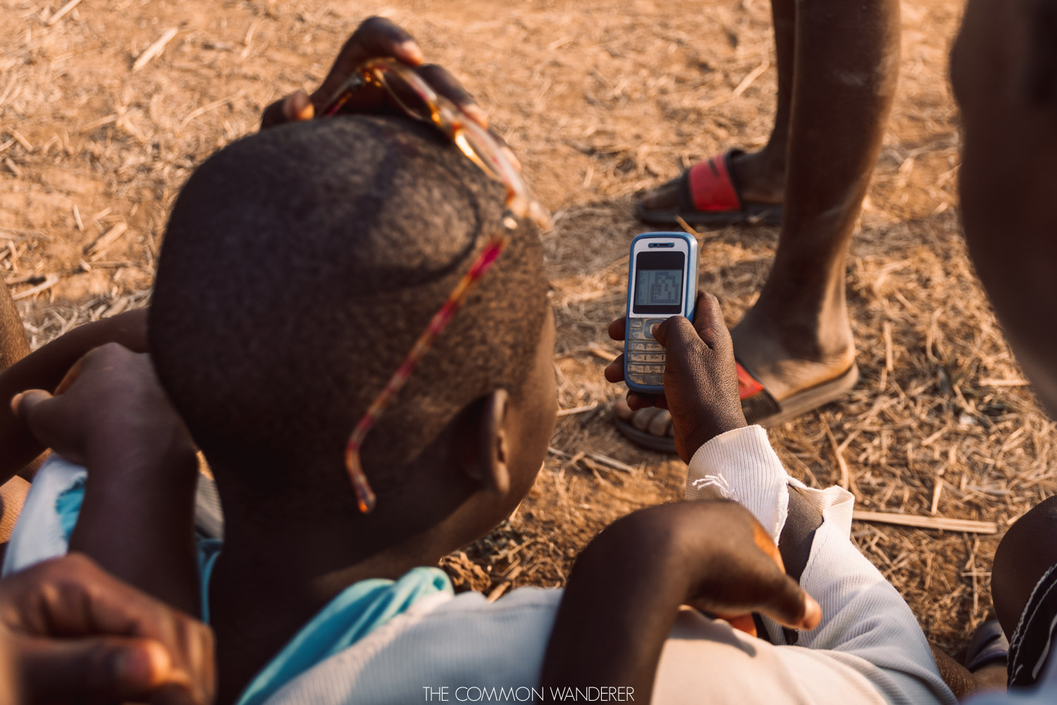 A young boy checks his phone in rural Malawi - Africa myths