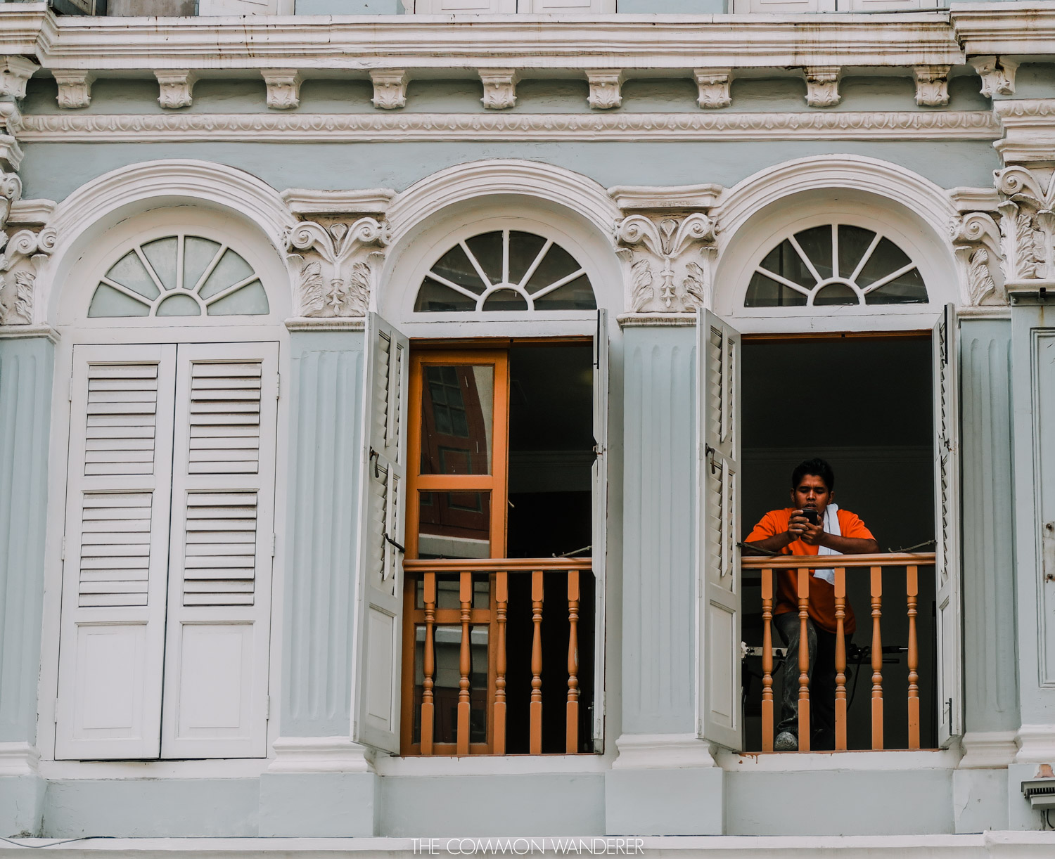 a man observing the streets from his window in Singapore