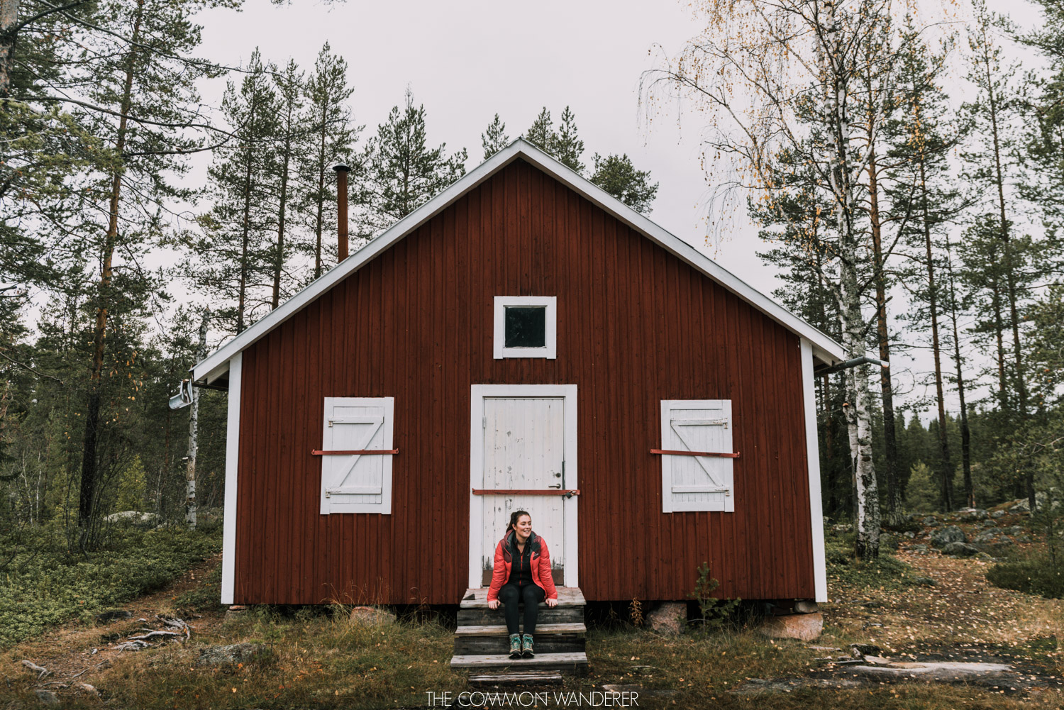 Lapland Pictures: girl sitting by red cabin in Storforsen, Swedish Lapland
