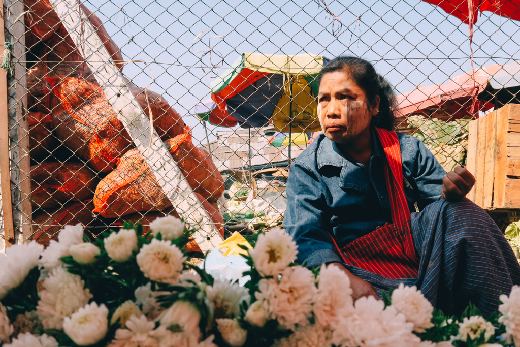 A woman sells flowers at a train station in Yangon, Myanmar