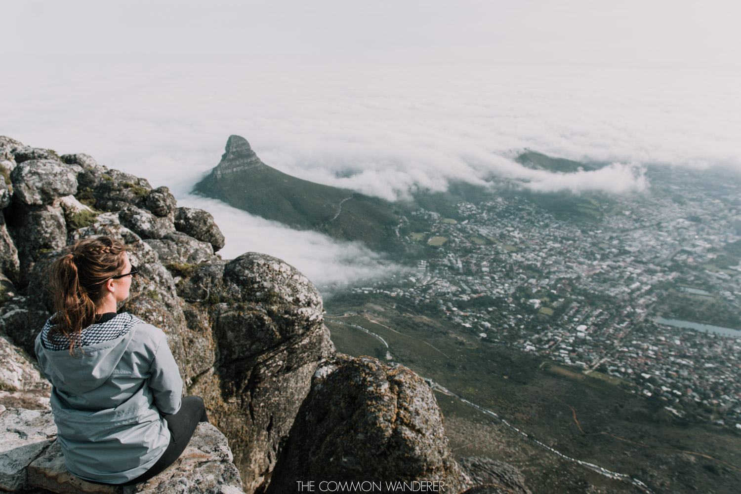 A woman sits on the edge of Table Mountain, Cape Town - The Common Wanderer
