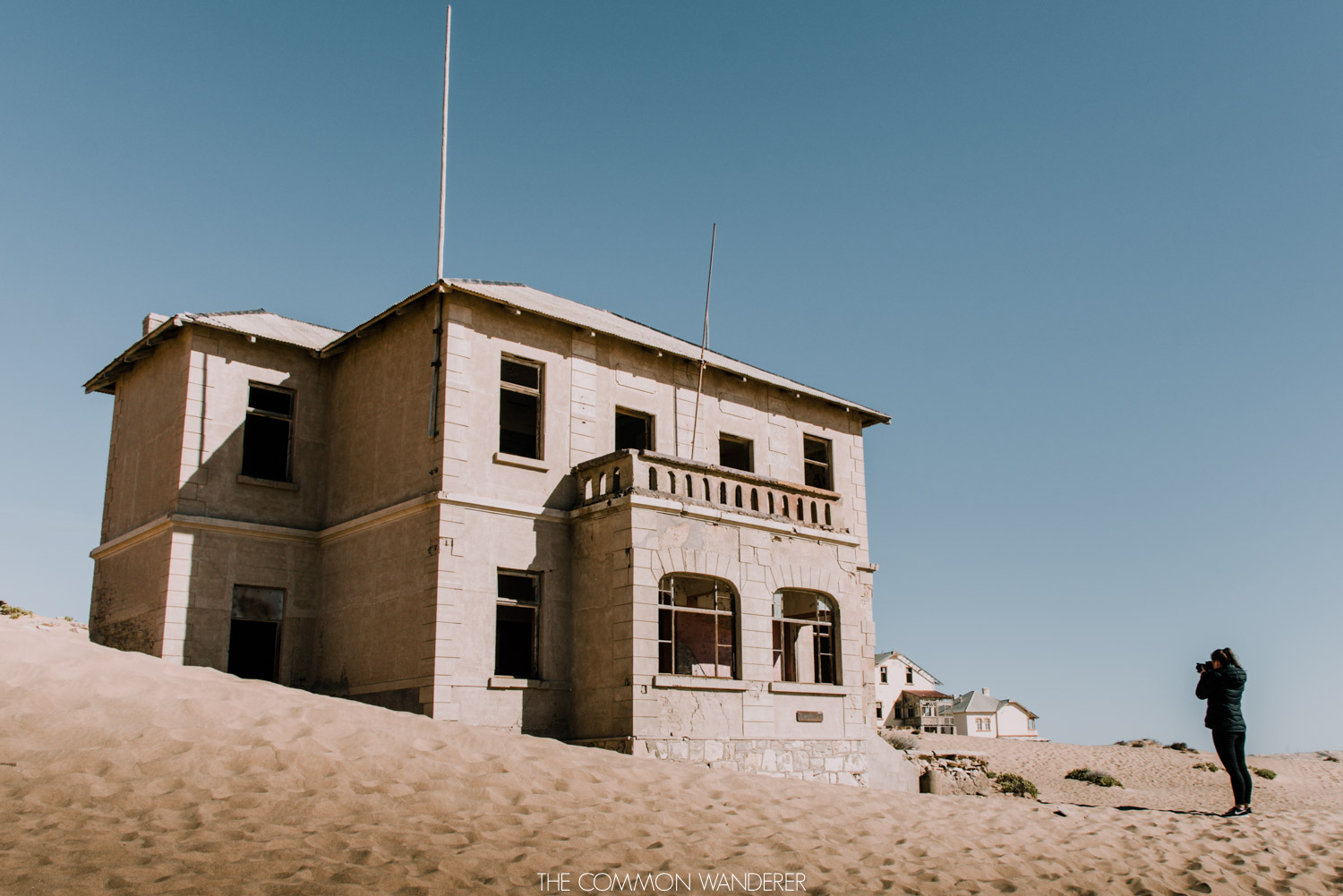 A woman takes a photo in Kolmanskop town, Namibia - the Common Wanderer